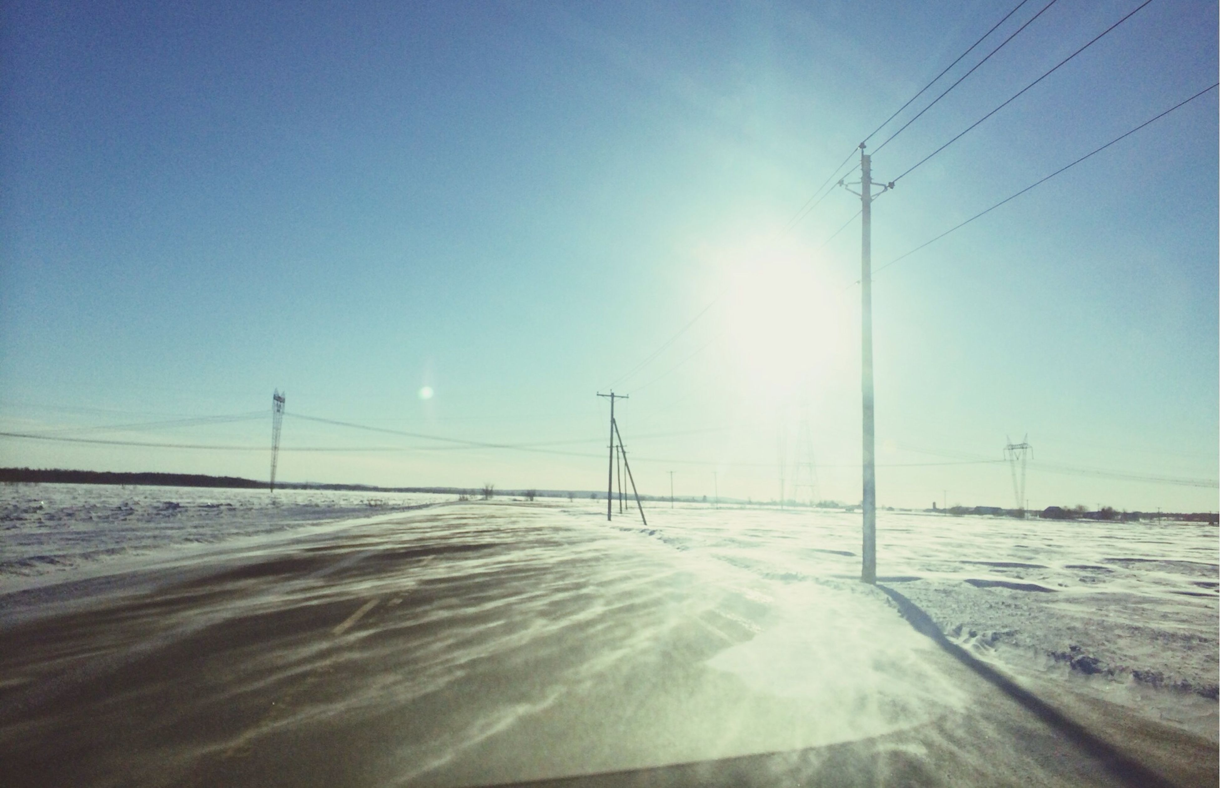sun, snow, electricity pylon, cold temperature, winter, sunlight, electricity, sunbeam, clear sky, sky, tranquility, power line, nature, blue, tranquil scene, lens flare, road, beauty in nature, fuel and power generation, scenics