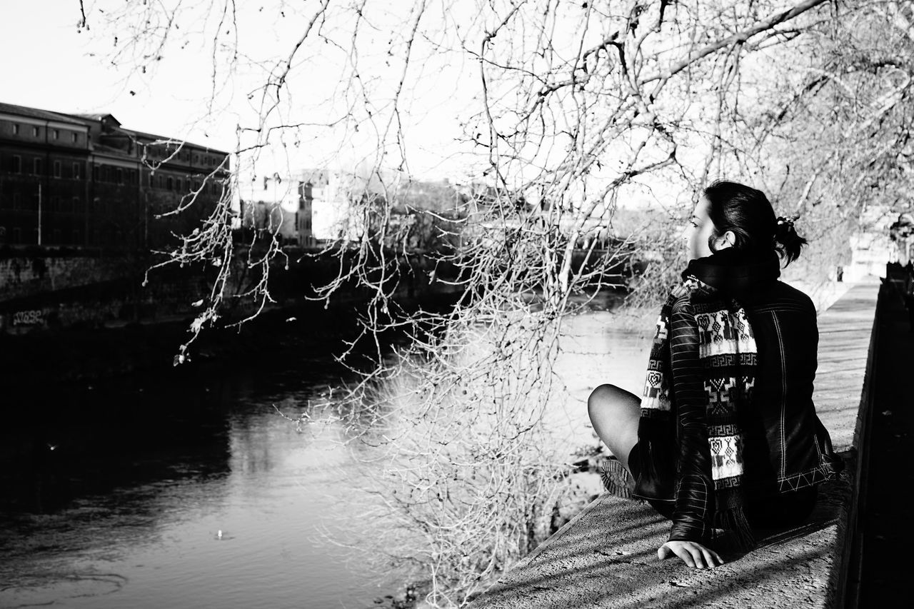 Rear View Of Woman Sitting On Retaining Wall By River Against Sky