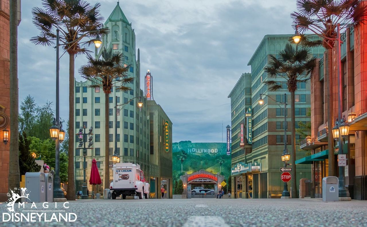 building exterior, architecture, street, transportation, built structure, palm tree, car, outdoors, land vehicle, illuminated, dusk, city, tree, mode of transport, street light, road, day, sky, no people