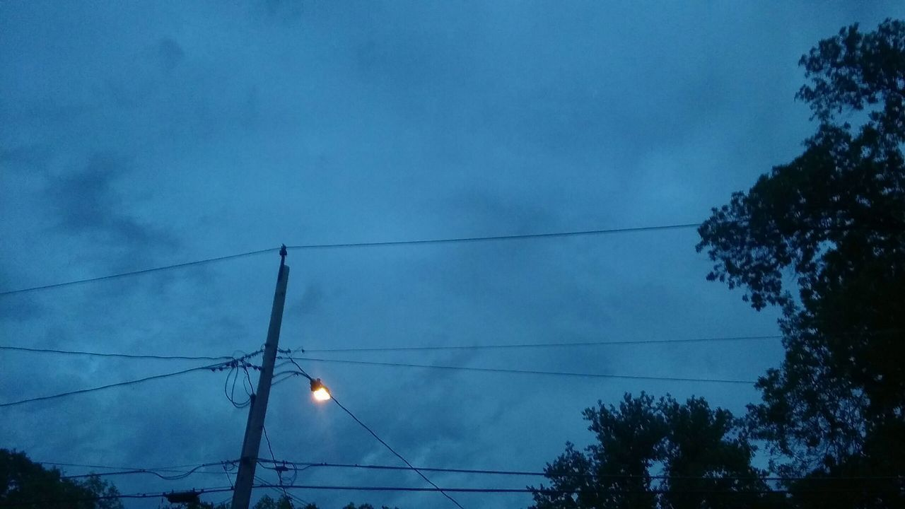 low angle view, power line, electricity, tree, sky, electricity pylon, power supply, silhouette, cable, connection, power cable, blue, cloud - sky, fuel and power generation, nature, dusk, sunset, technology, street light, tranquility