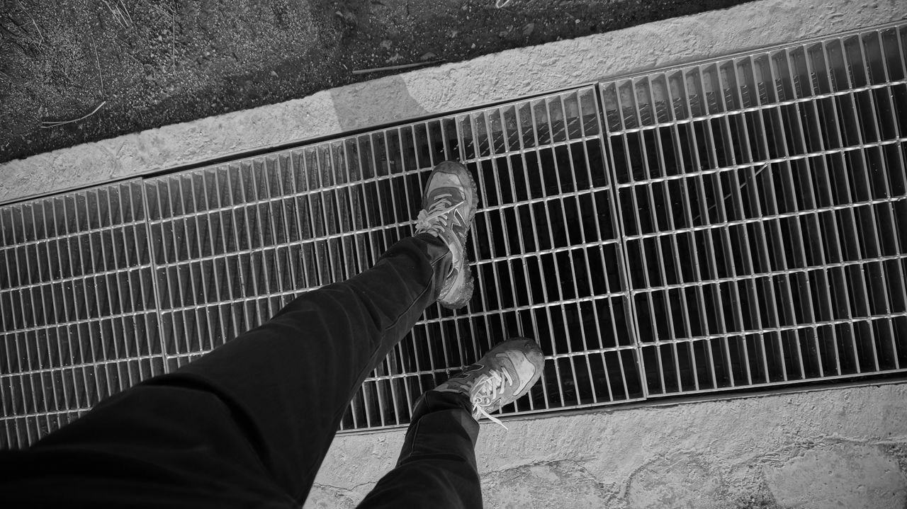 low section, personal perspective, person, shoe, lifestyles, men, standing, unrecognizable person, leisure activity, high angle view, part of, metal, human foot, directly above, railing, day, street