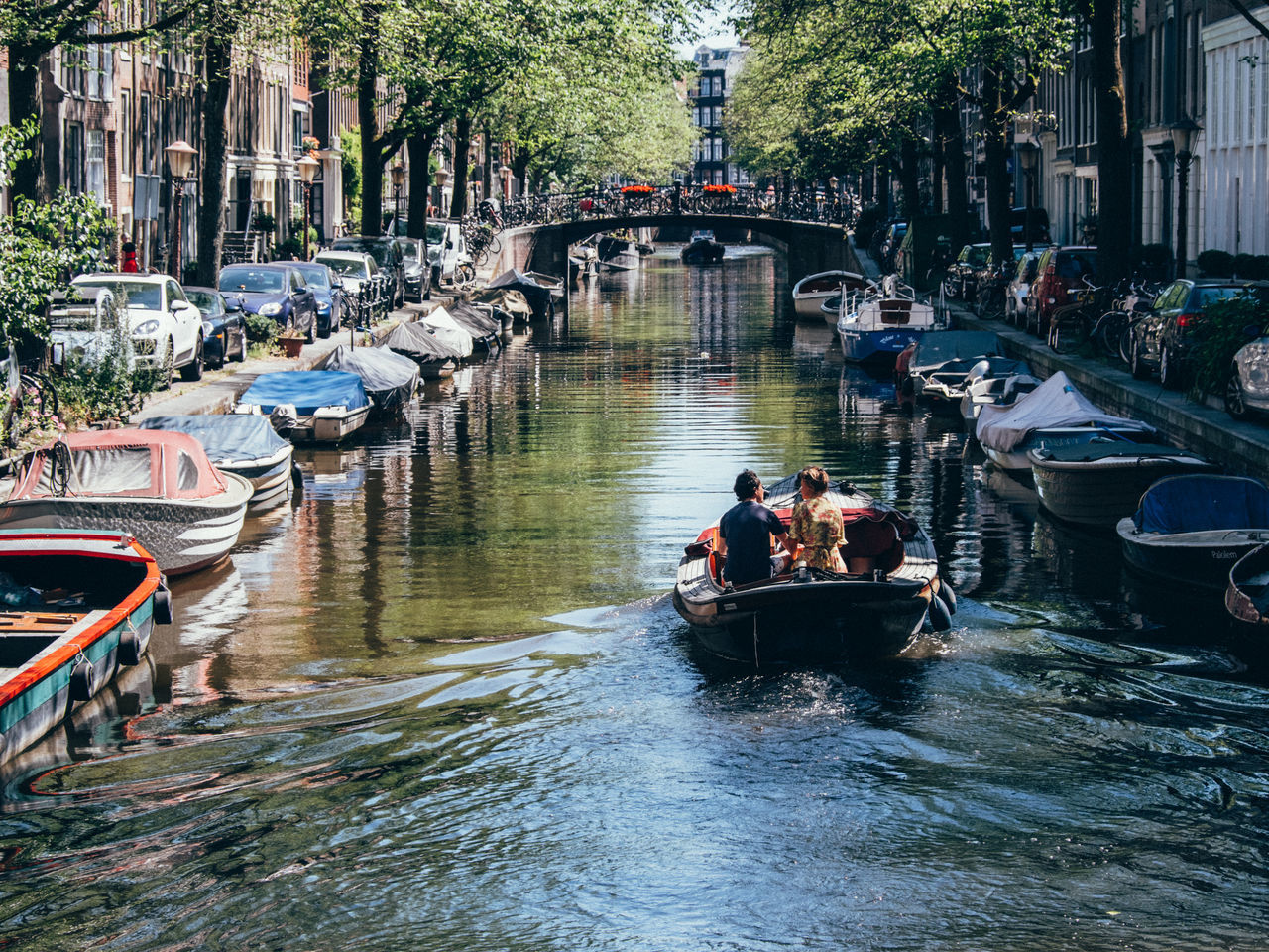 Amsterdam Architecture Bridge - Man Made Structure Building Exterior Built Structure Canal Day Gondola - Traditional Boat Leisure Activity Lifestyles Mode Of Transport Nature Nautical Vessel Netherlands Outdoors People Real People Transportation Tree Water Waterfront