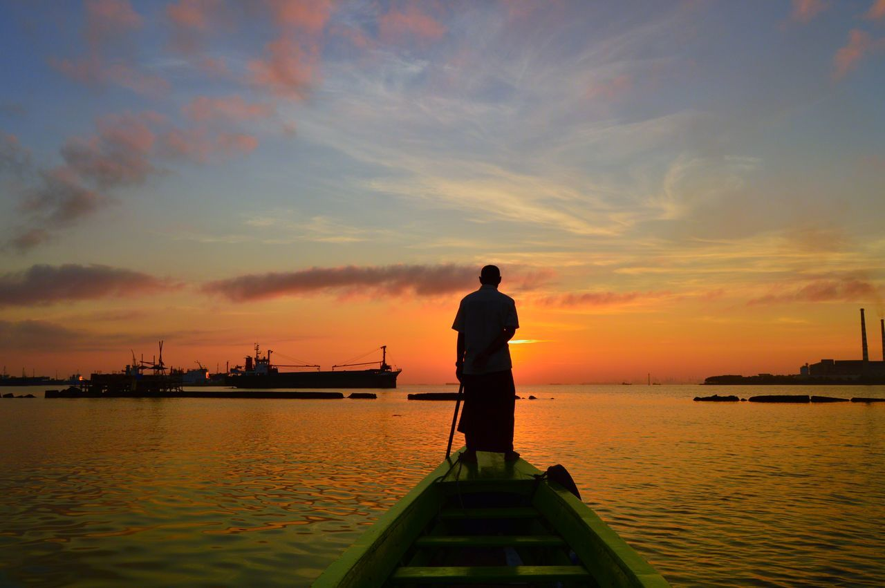 Rear View Of Fisherman Fishing In Sea During Sunset