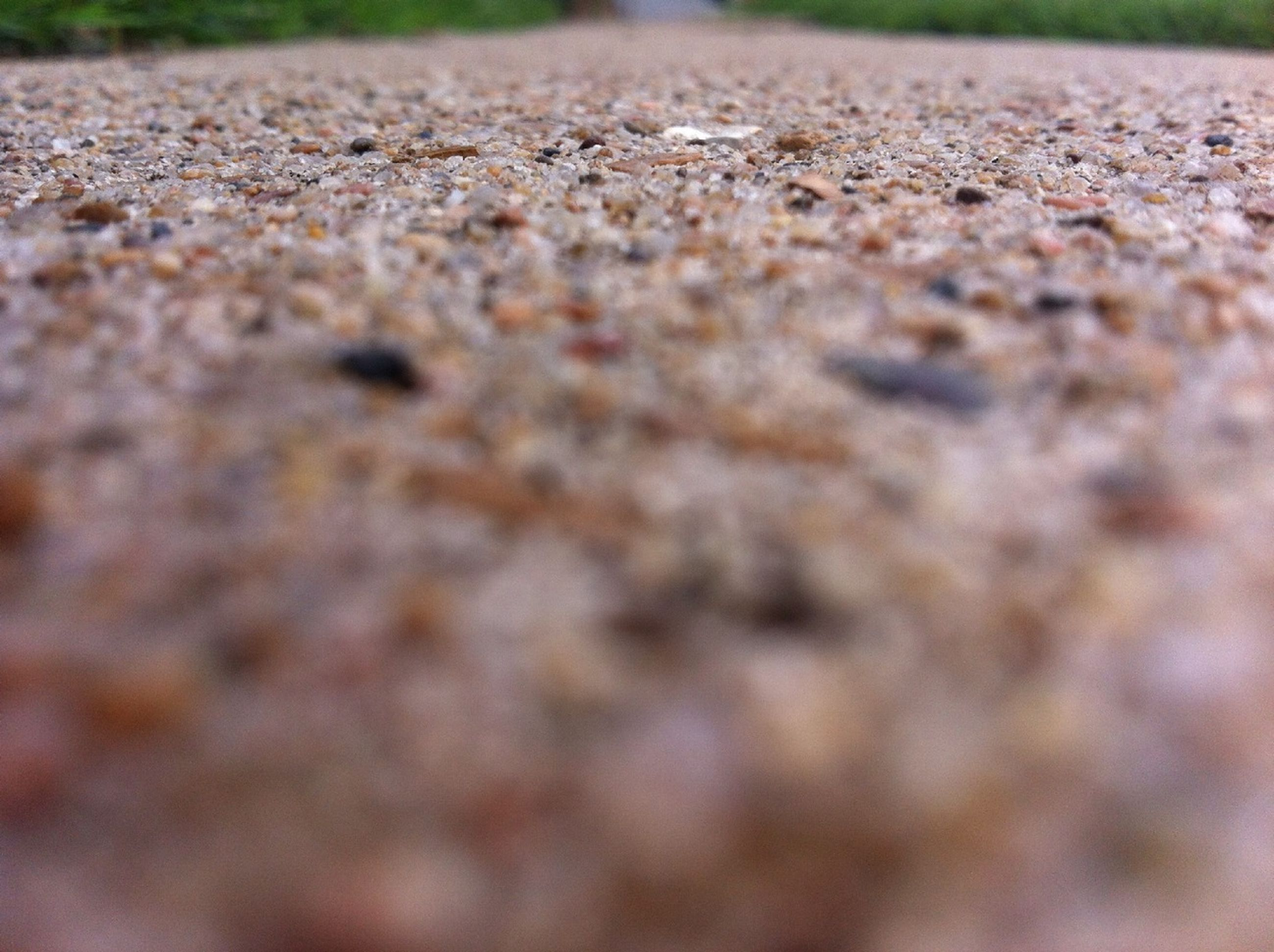 surface level, selective focus, textured, close-up, full frame, backgrounds, day, outdoors, focus on foreground, high angle view, nature, no people, street, asphalt, pattern, road, pebble, stone - object, tranquility, field