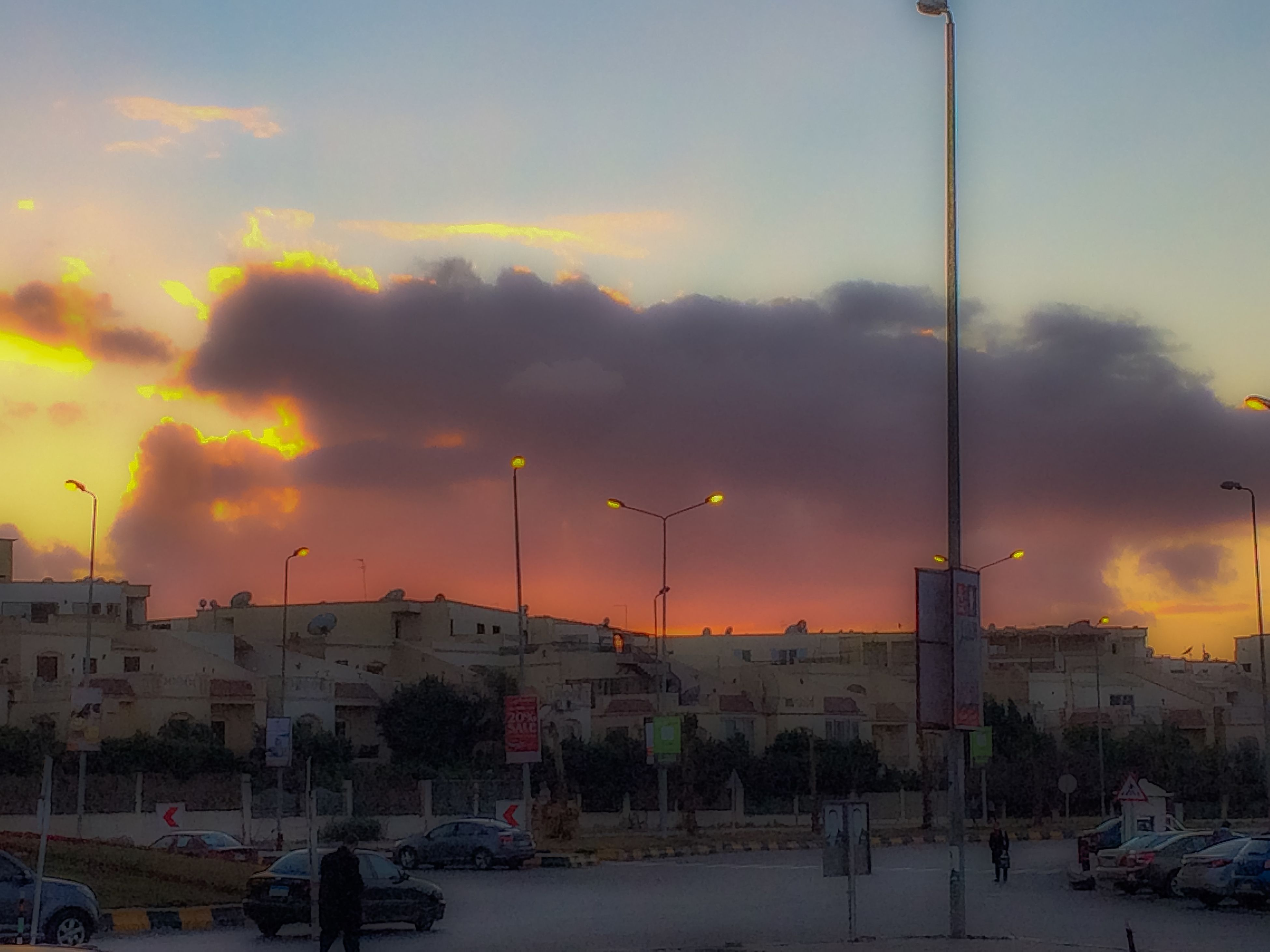 sunset, transportation, sky, mode of transport, cloud - sky, street light, car, orange color, weather, land vehicle, built structure, cloudy, building exterior, city, architecture, street, outdoors, harbor, in a row, nature