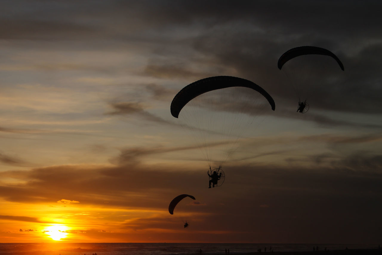 sunset, parachute, sky, extreme sports, mid-air, adventure, paragliding, flying, cloud - sky, silhouette, gliding, nature, exhilaration, leisure activity, dramatic sky, freedom, one person, outdoors, scenics, real people, beauty in nature, low angle view, sport, sea, skydiving, day, people