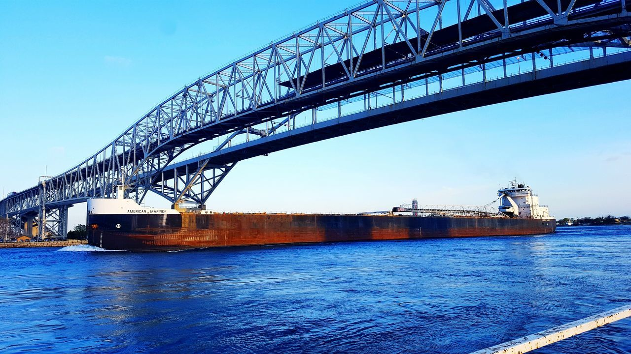 Frieghter going under the Blue Water Bridge. Connection Architecture Built Structure Bridge - Man Made Structure Water River Engineering Low Angle View Transportation Waterfront City Travel Destinations Bridge Day Outdoors Blue Sky Riverbank Nature Suspension Bridge Blue Water Bridge Port Huron Michigan Freighter