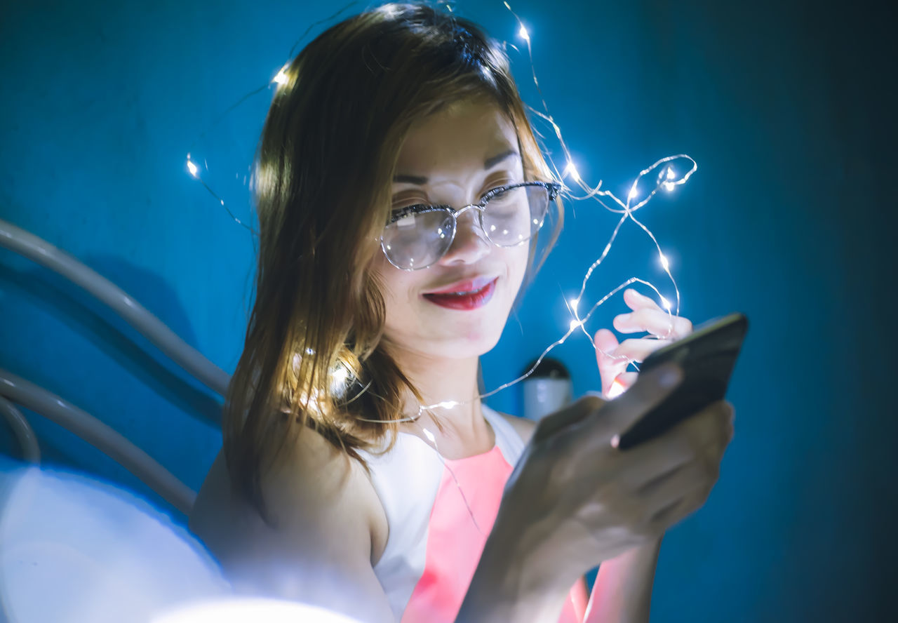 holding, young adult, wireless technology, one person, blond hair, real people, front view, young women, night, studio shot, illuminated, blue, technology, indoors, close-up