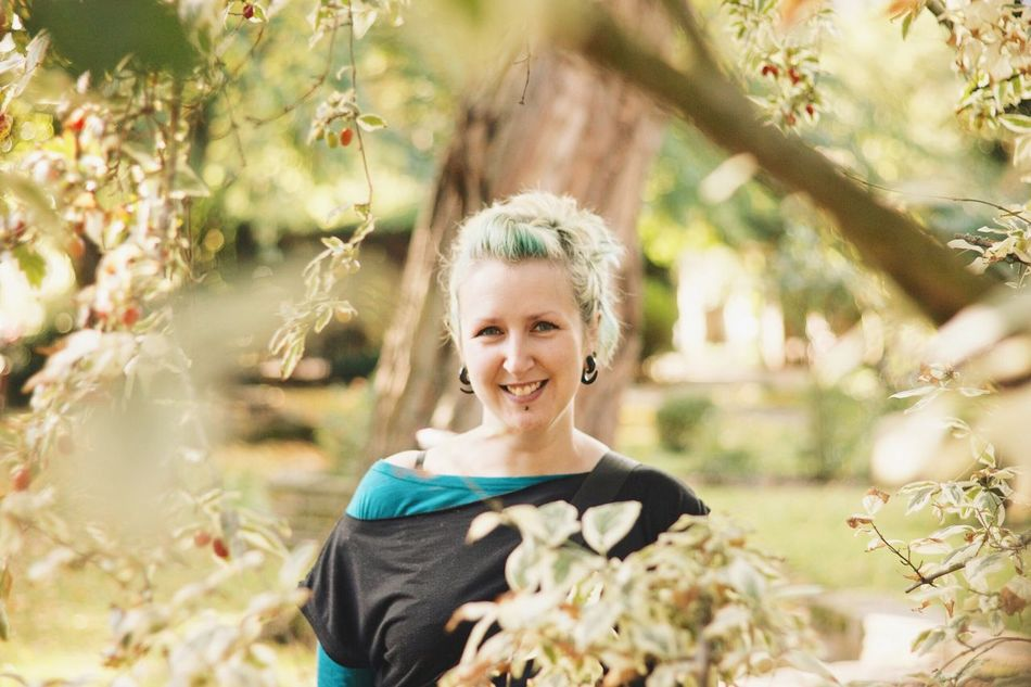 My wife, grinning at me through the leaves. Portrait Of A Woman Nature Trees Leaves Smile Blue Hair