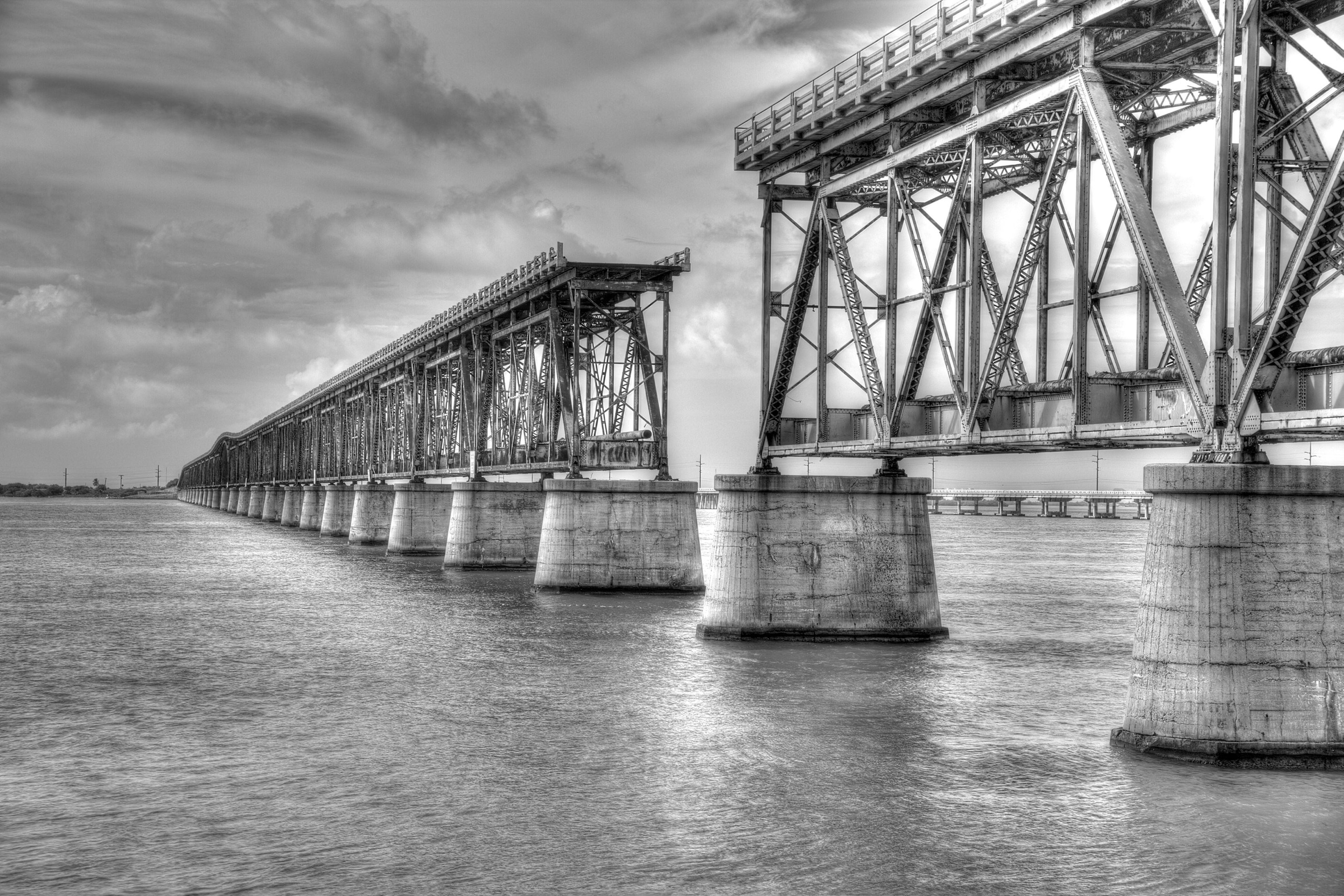 architecture, built structure, water, waterfront, sky, connection, bridge - man made structure, cloud - sky, river, bridge, transportation, reflection, engineering, rippled, low angle view, cloudy, cloud, no people, outdoors, day