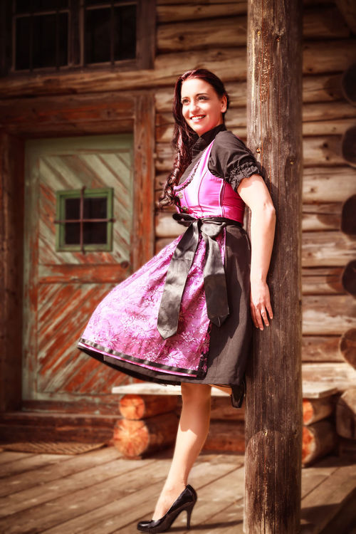 Young dark-haired woman in elegant dirndl on the terrace of a log cabin Architecture Bavaria Beautiful Woman Building Exterior Built Structure Day Dirndl Full Length Happiness House Leisure Activity Lifestyles Looking At Camera One Person Outdoors People Portrait Posing Real People Smiling Standing Woman Wood - Material Young Adult Young Women