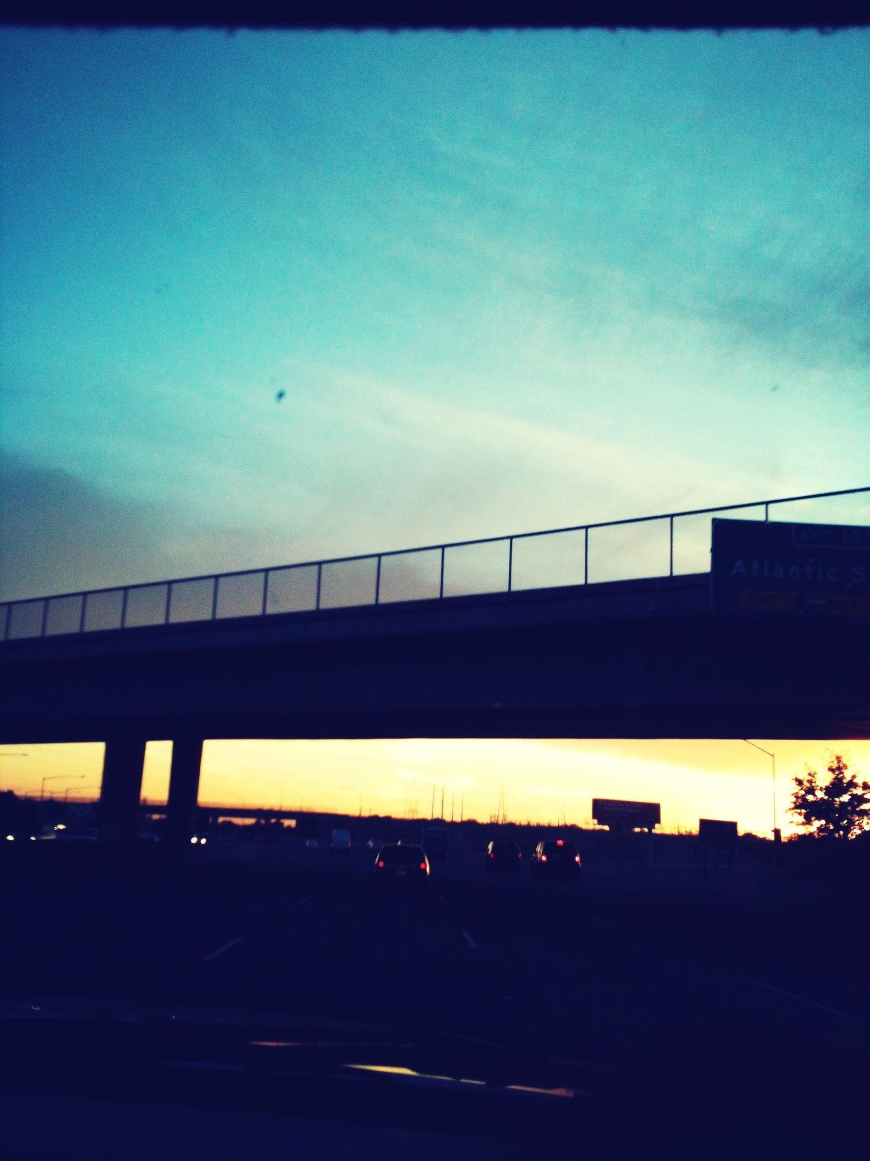architecture, built structure, bridge - man made structure, sky, connection, low angle view, transportation, silhouette, bridge, engineering, dusk, sunset, building exterior, illuminated, cloud - sky, blue, city, no people, cloud, railing