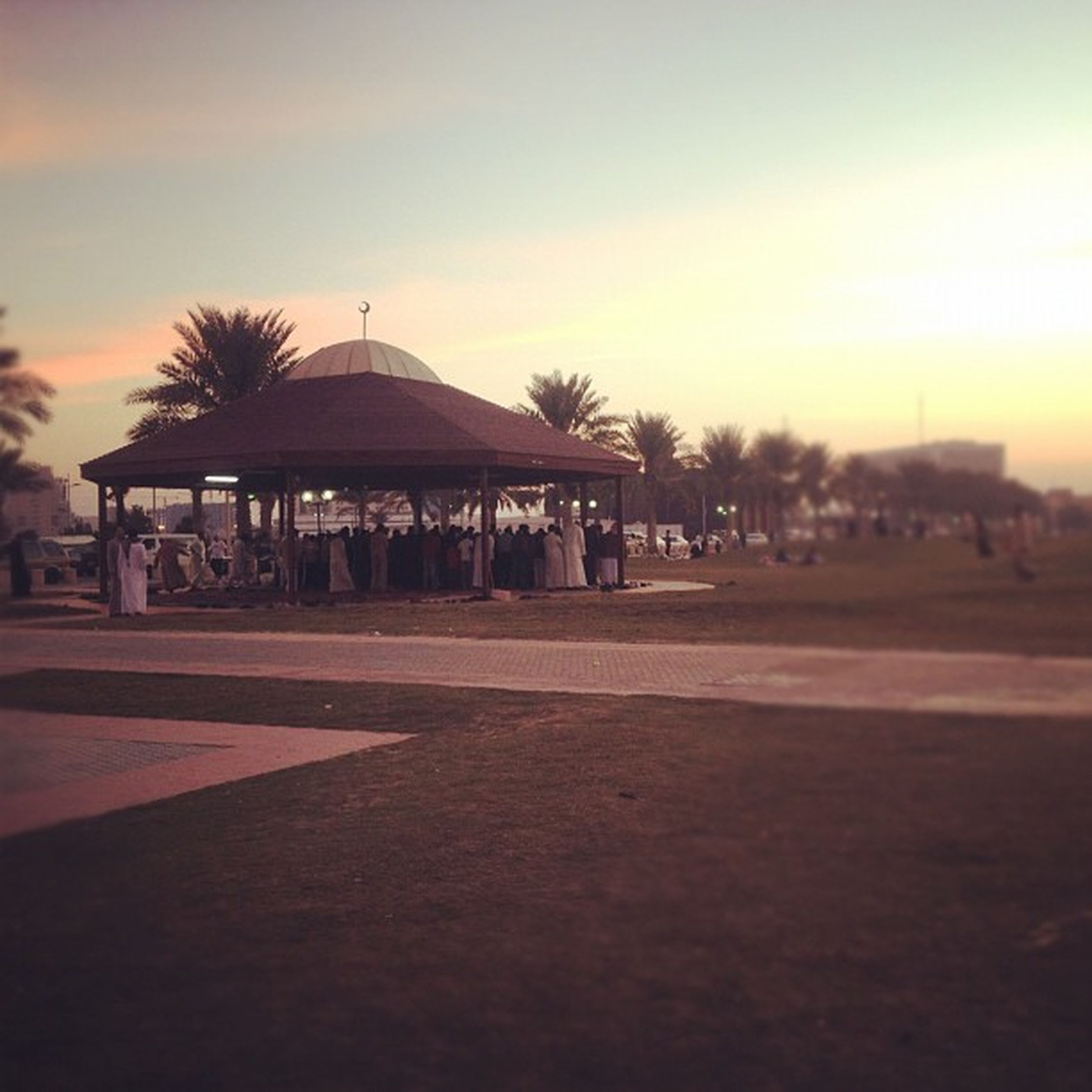 sunset, building exterior, sky, architecture, built structure, tree, incidental people, large group of people, palm tree, dusk, outdoors, beach, city, street, water, street light, lifestyles, person, sea