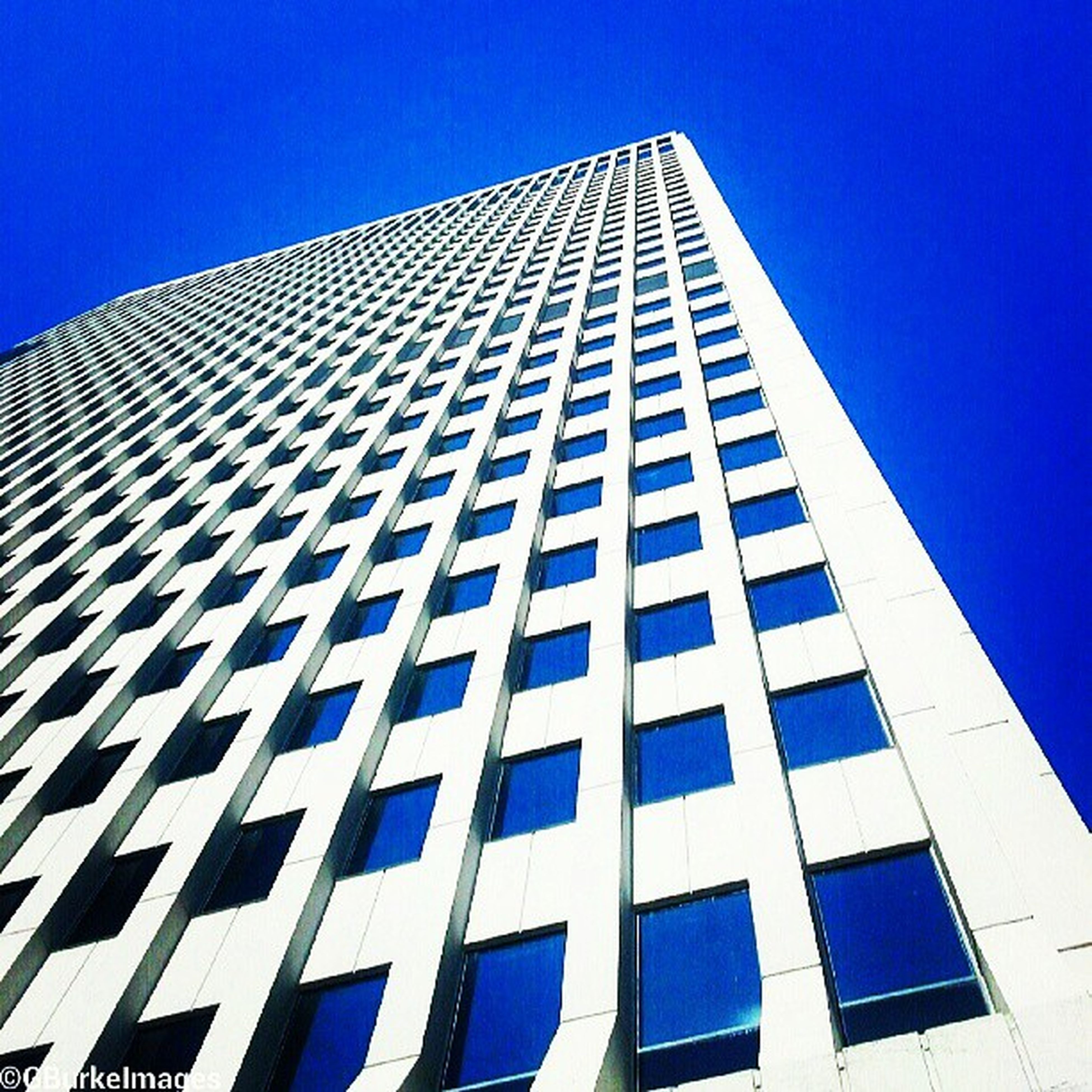 architecture, building exterior, built structure, low angle view, modern, office building, clear sky, skyscraper, city, blue, tall - high, tower, building, glass - material, repetition, reflection, window, day, pattern, outdoors