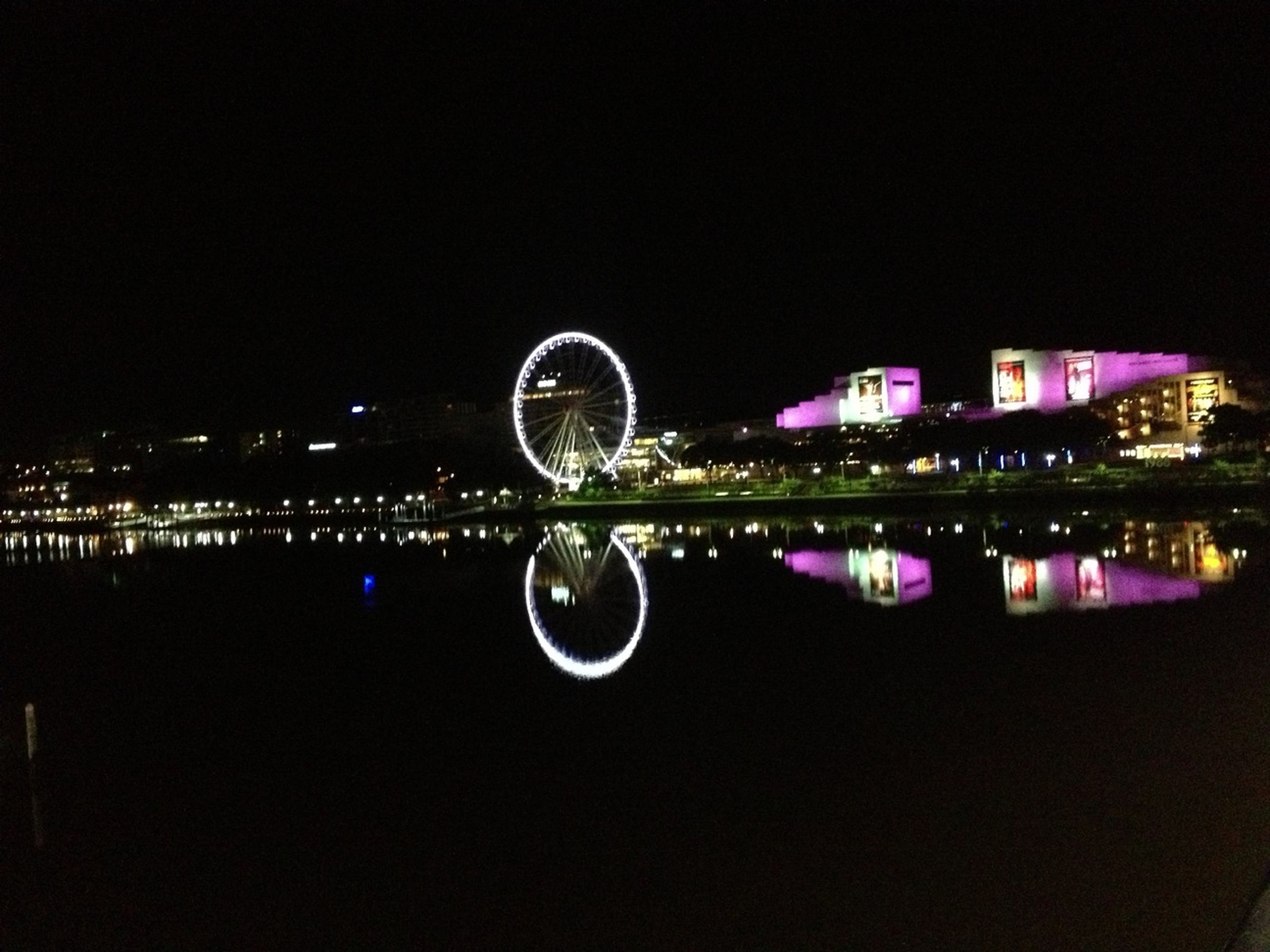 water, night, illuminated, reflection, building exterior, waterfront, city, clear sky, copy space, architecture, built structure, circle, sky, cityscape, no people, blue, outdoors, river, multi colored, motion