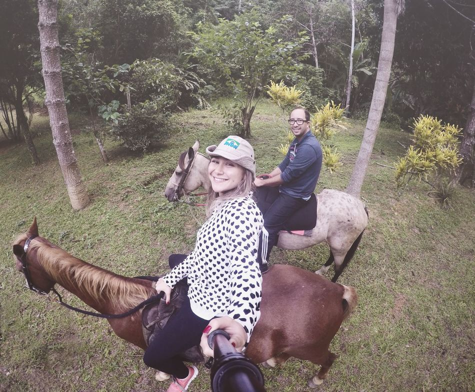 Horse Togetherness Two People Day Leisure Activity Smiling Riding Bonding Animal Themes Casual Clothing Bicycle Love Domestic Animals Happiness Real People Outdoors Lifestyles Dog Tree Sitting Young Adult