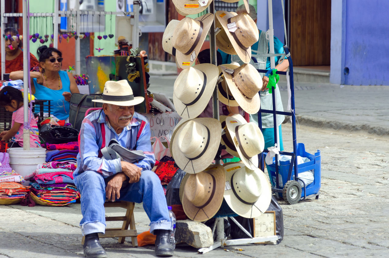 hat, one person, real people, front view, sitting, full length, occupation, men, skill, outdoors, day, musical instrument, headwear, musician, one man only, adult, people