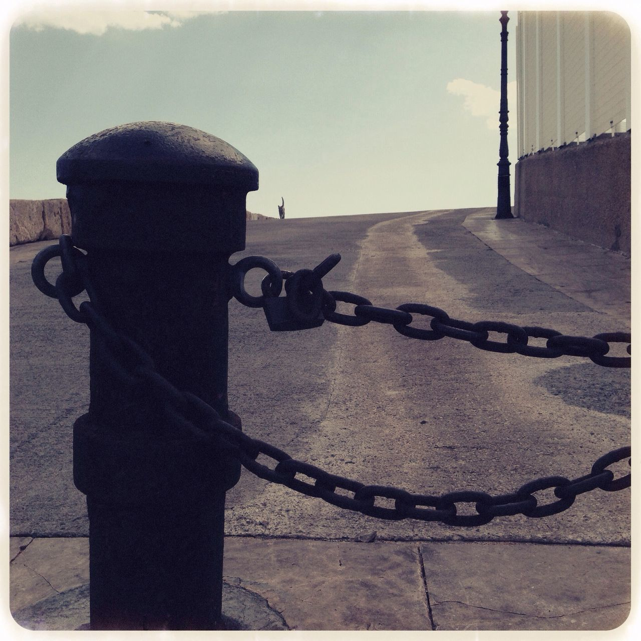 Chain Attached To Bollard On Street Against Sky