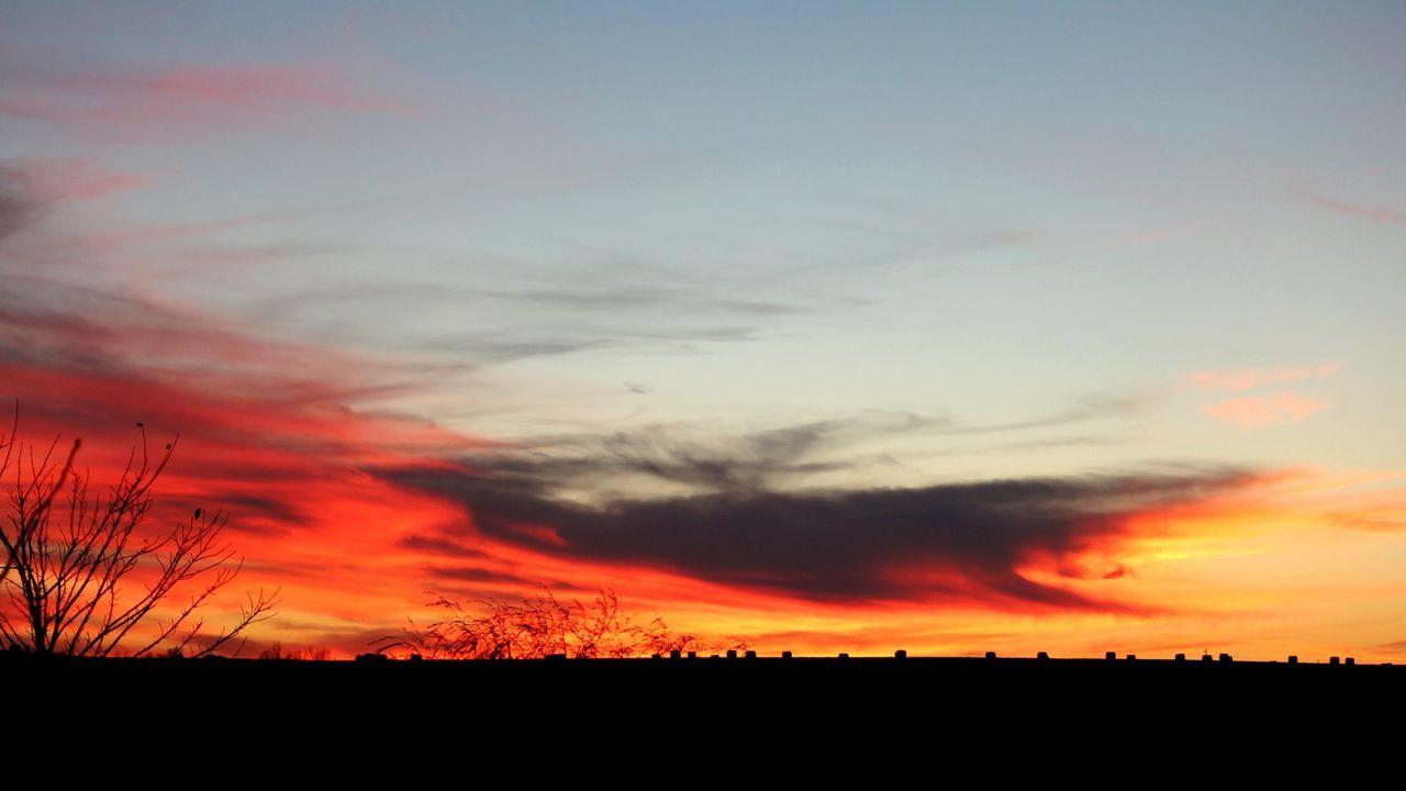 Silhouette Landscape Against Orange Sky During Sunset