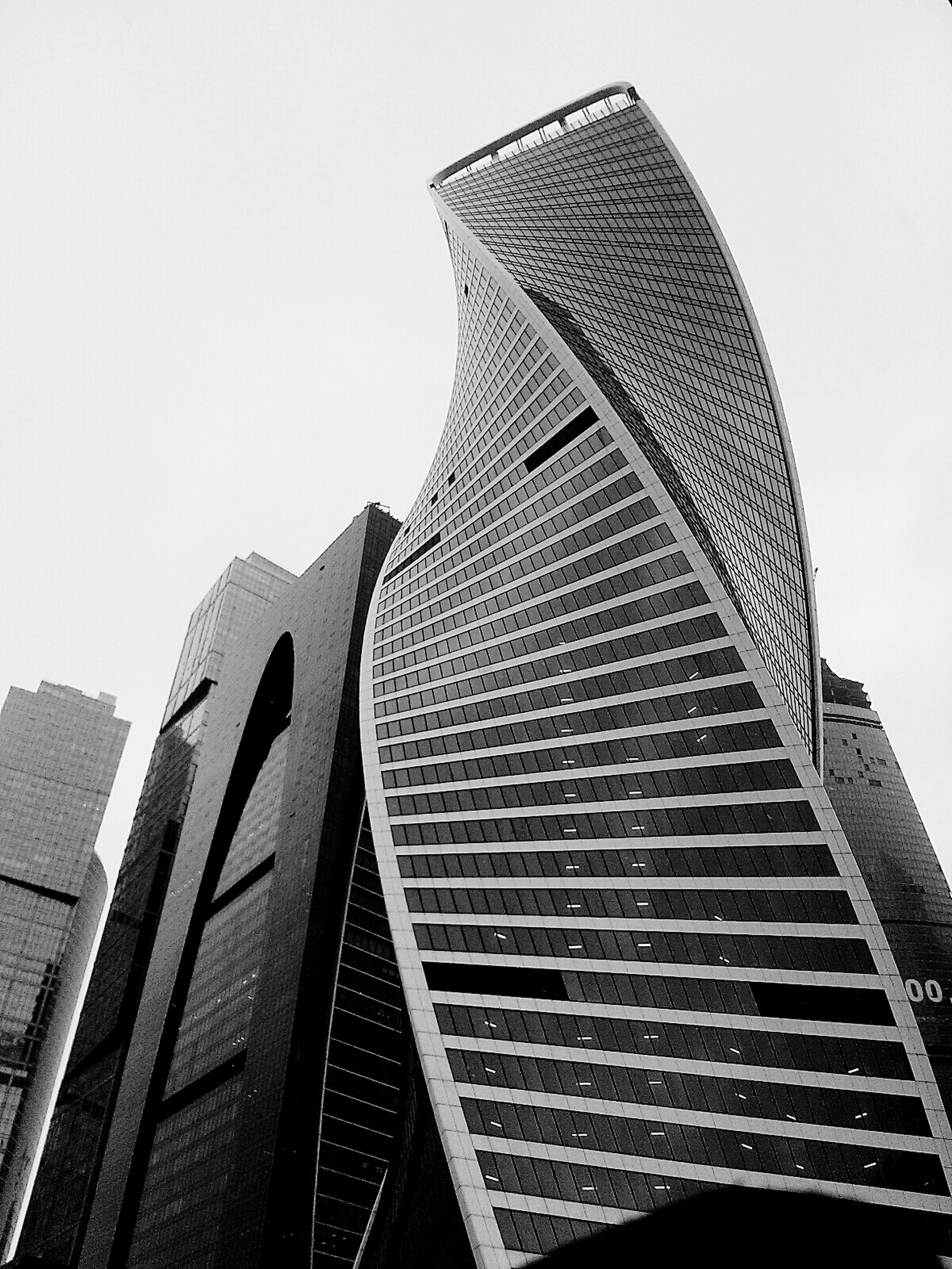 low angle view, building exterior, architecture, built structure, skyscraper, tall - high, modern, clear sky, tower, office building, city, tall, building, day, sky, outdoors, glass - material, development, no people, architectural feature