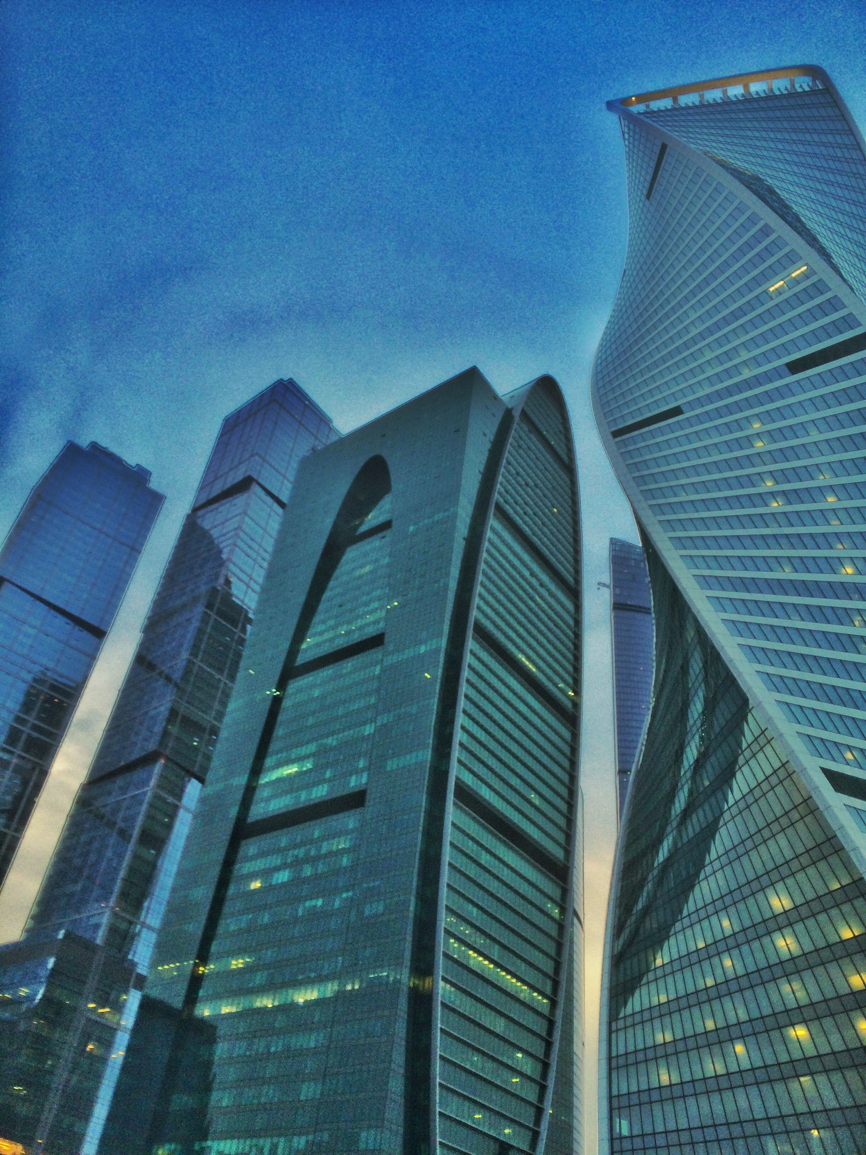 architecture, building exterior, built structure, low angle view, modern, skyscraper, office building, city, tall - high, sky, tower, blue, building, glass - material, cloud - sky, no people, outdoors, capital cities, tall, day