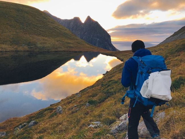 Mountain Hiking Mountain Range Beauty In Nature Nature Scenics Rear View Backpack Lofoten Islands Norway Colorful Water Reflections Leisure Activity Travel Adventure Rock - Object Landscape Sky Looking At View Cloud - Sky Men Vacations Outdoors