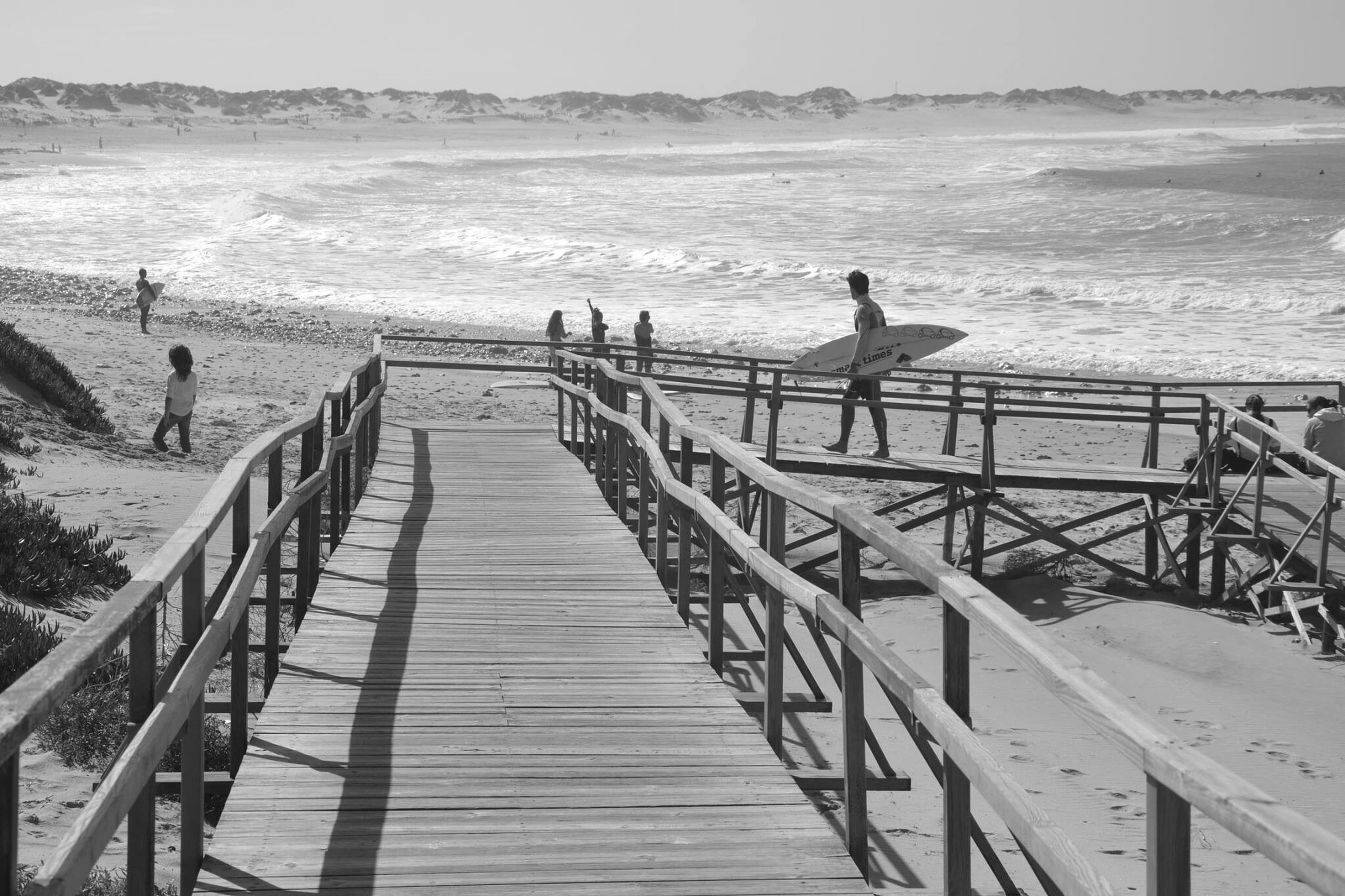 sea, beach, water, sand, shore, leisure activity, pier, horizon over water, railing, tranquil scene, scenics, tranquility, vacations, lifestyles, nature, wood - material, beauty in nature, person, boardwalk
