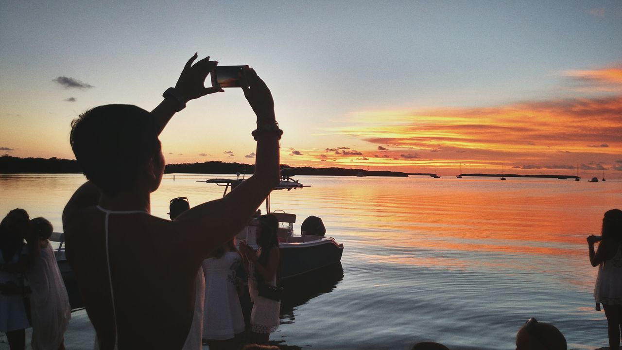 sunset, water, sea, silhouette, sky, real people, orange color, leisure activity, horizon over water, nature, togetherness, cloud - sky, men, scenics, lifestyles, outdoors, beauty in nature, women, nautical vessel, large group of people, beach, friendship, human hand, day, people