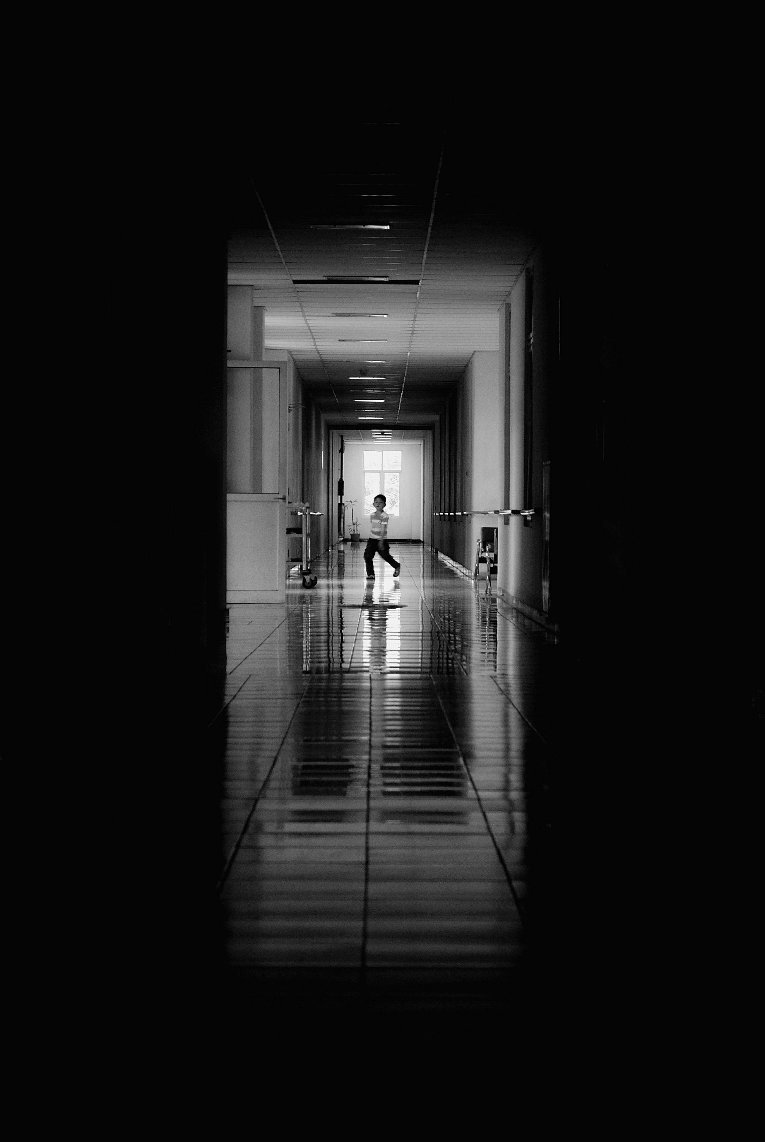 indoors, walking, men, full length, lifestyles, corridor, the way forward, architecture, dark, silhouette, built structure, rear view, tunnel, wall - building feature, person, illuminated, leisure activity