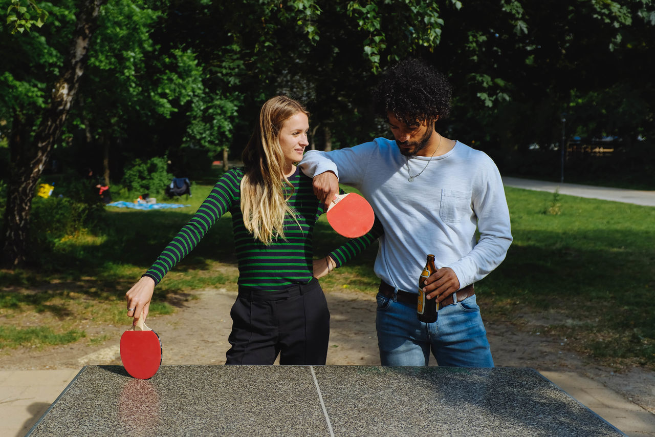 Adult Ball Bonding Casual Clothing Day Friendship Front View Fun Happiness Holding Leisure Activity Men Outdoors Playing Real People Smiling Standing Togetherness Tree Two People Young Adult Young Men Young Women