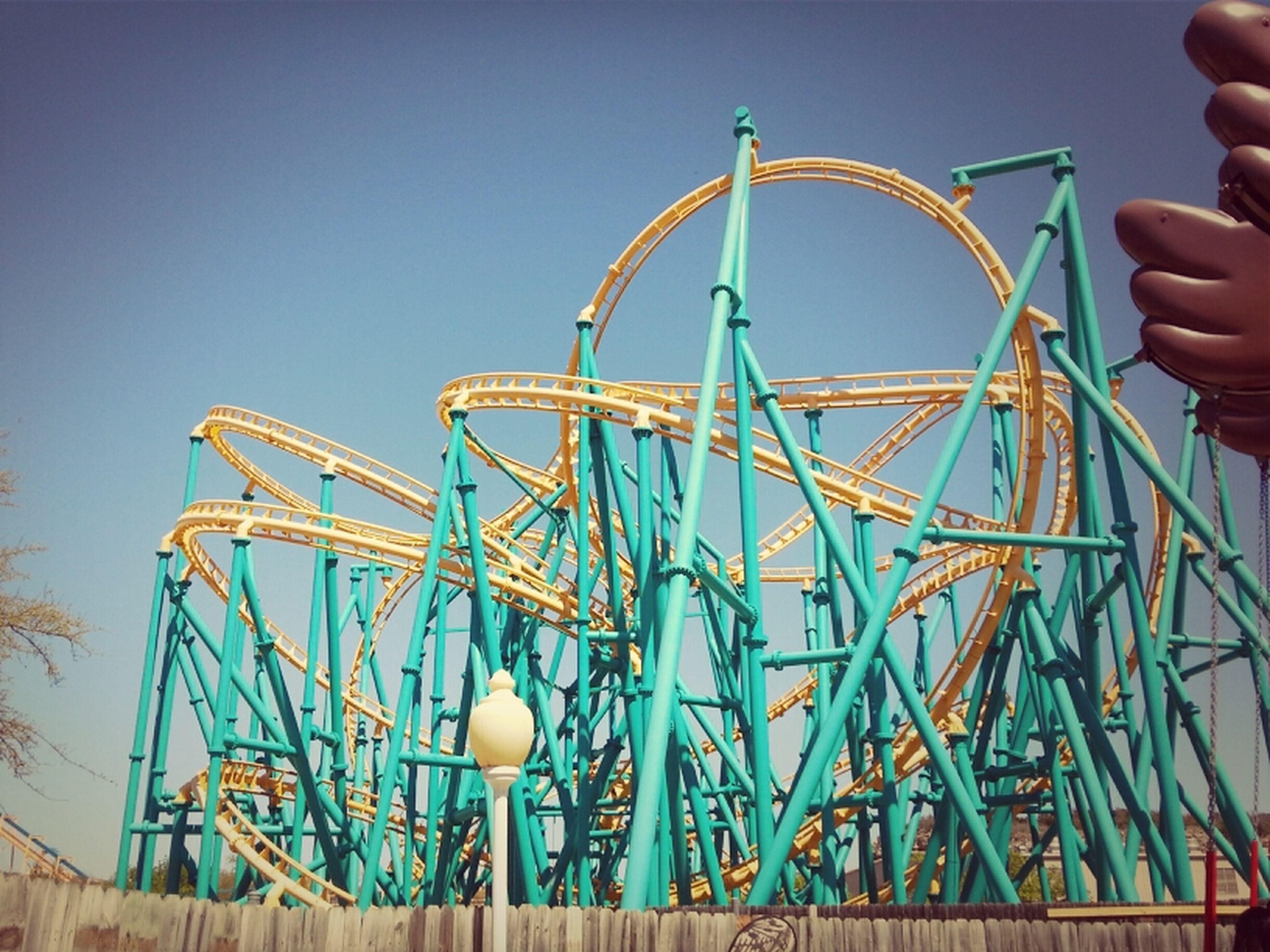 clear sky, low angle view, amusement park, blue, metal, amusement park ride, arts culture and entertainment, sky, ferris wheel, part of, cropped, copy space, leisure activity, built structure, metallic, outdoors, day, person