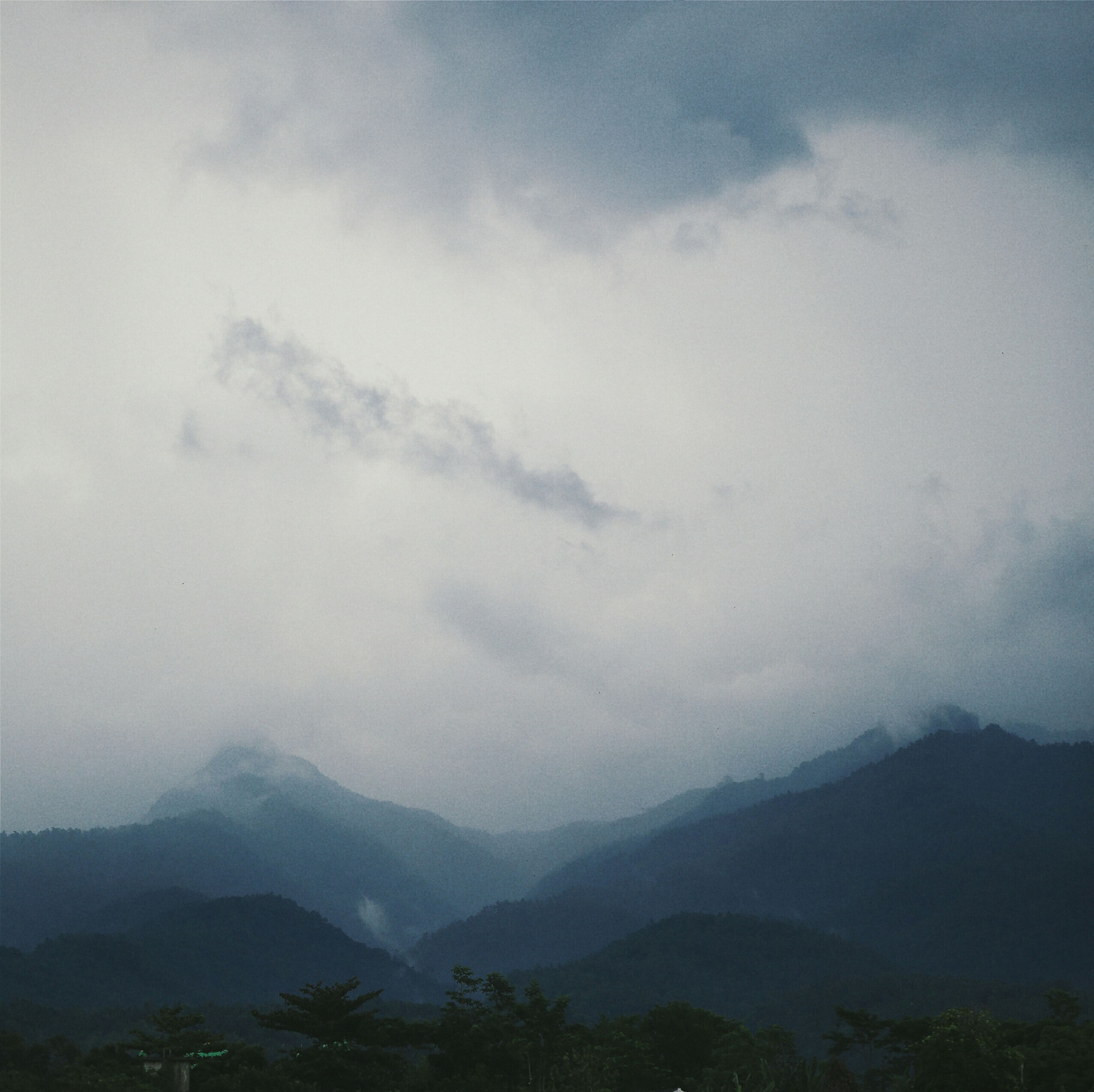 mountain, mountain range, scenics, tranquil scene, tranquility, beauty in nature, sky, landscape, nature, cloud - sky, non-urban scene, idyllic, tree, fog, cloudy, cloud, weather, outdoors, remote, day
