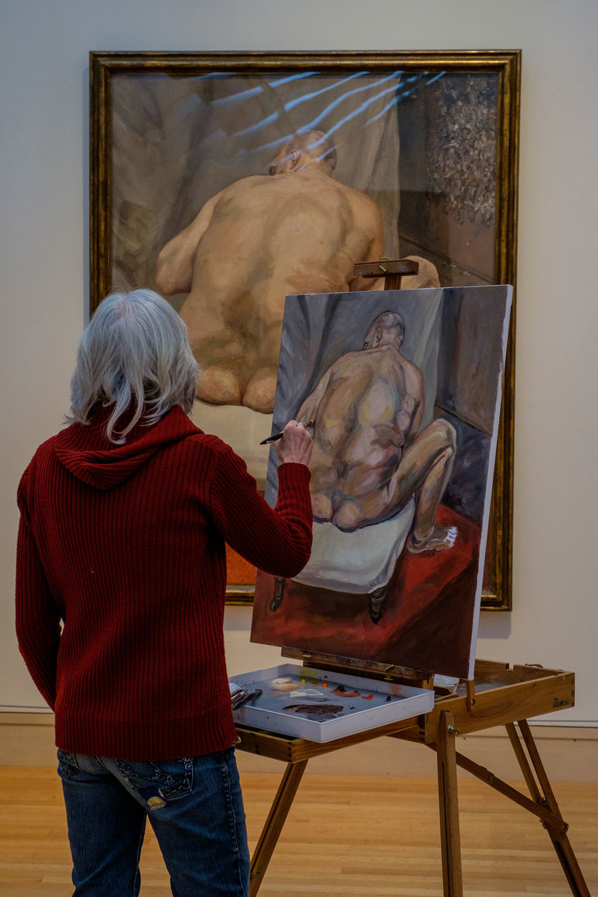 senior adult, senior women, artist, one person, easel, indoors, rear view, real people, leisure activity, paintbrush, museum, artist's canvas, casual clothing, fine art painting, lifestyles, standing, art studio, arts culture and entertainment, women, photograph, day, adult, people, adults only