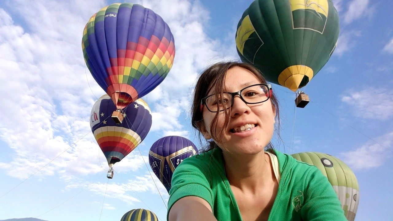 hot air balloon, flying, cloud - sky, sky, one person, day, balloon, happiness, multi colored, low angle view, mid-air, outdoors, fun, smiling, headshot, cheerful, real people, young adult, young women, helium balloon, adult, people, ballooning festival, adults only