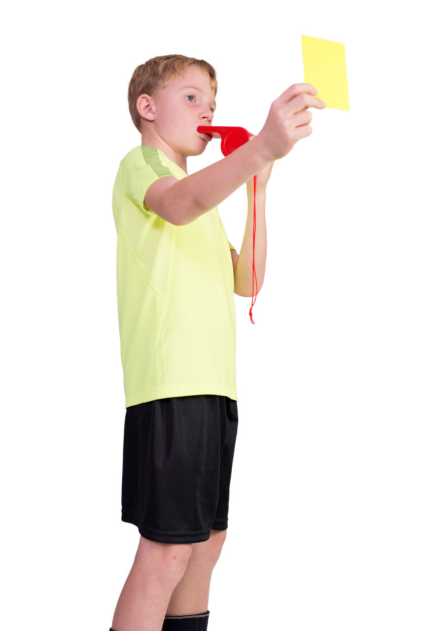 Low Angle View Of Boy Whistling And Showing Yellow Card Against White Background