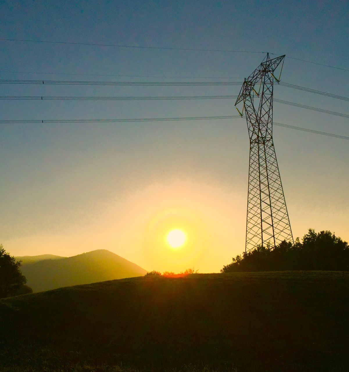 Low Angle View Of Electricity Pylon At Sunset
