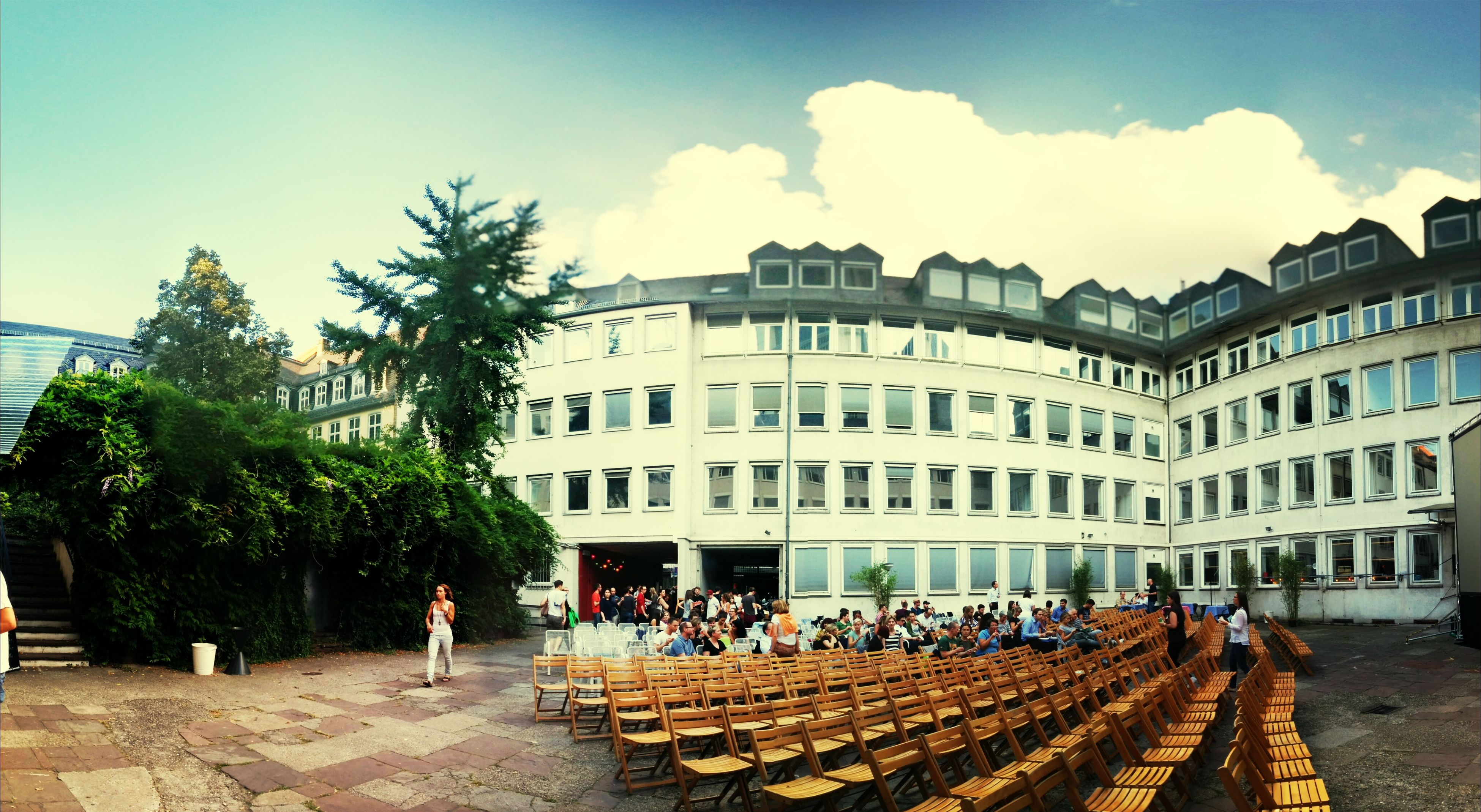 building exterior, architecture, built structure, sky, large group of people, person, city, men, cloud - sky, tree, lifestyles, city life, street, sunlight, cloud, day, outdoors, leisure activity, cobblestone