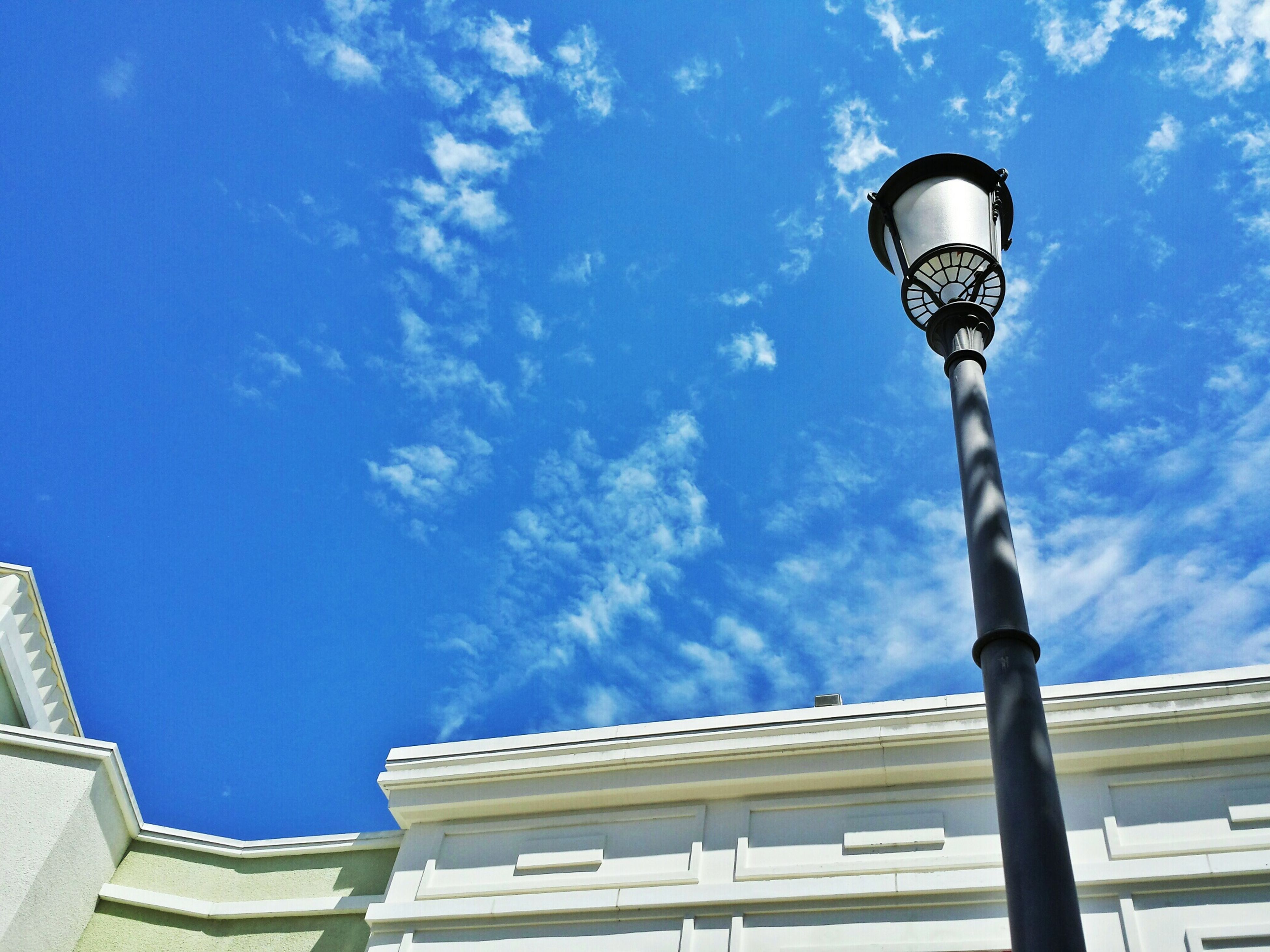 low angle view, architecture, building exterior, built structure, sky, street light, blue, lighting equipment, building, cloud - sky, high section, residential building, city, cloud, day, outdoors, no people, residential structure, sunlight, tower