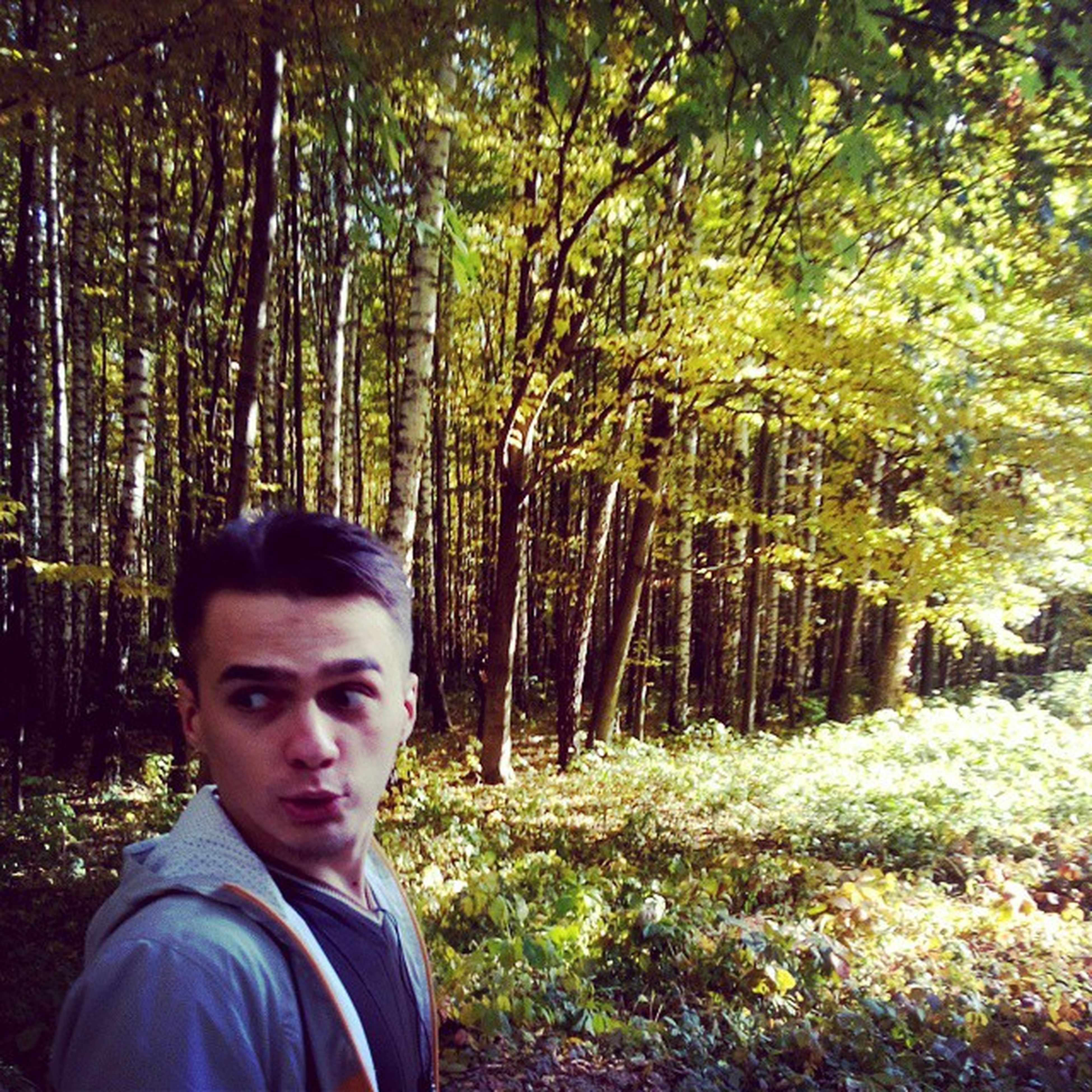 tree, person, lifestyles, leisure activity, looking at camera, portrait, casual clothing, young adult, forest, headshot, front view, smiling, young men, growth, standing, boys, green color, happiness