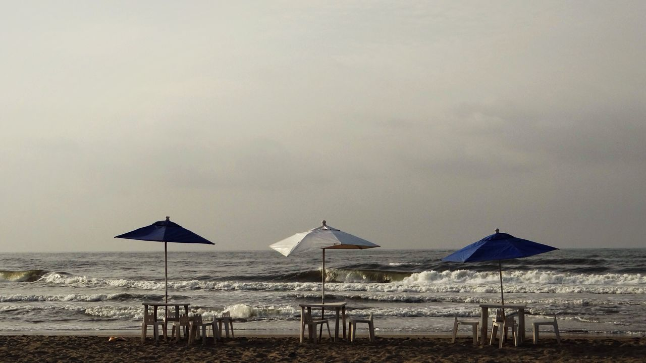 Tables And Chairs Under Parasols On Beach Against Sky