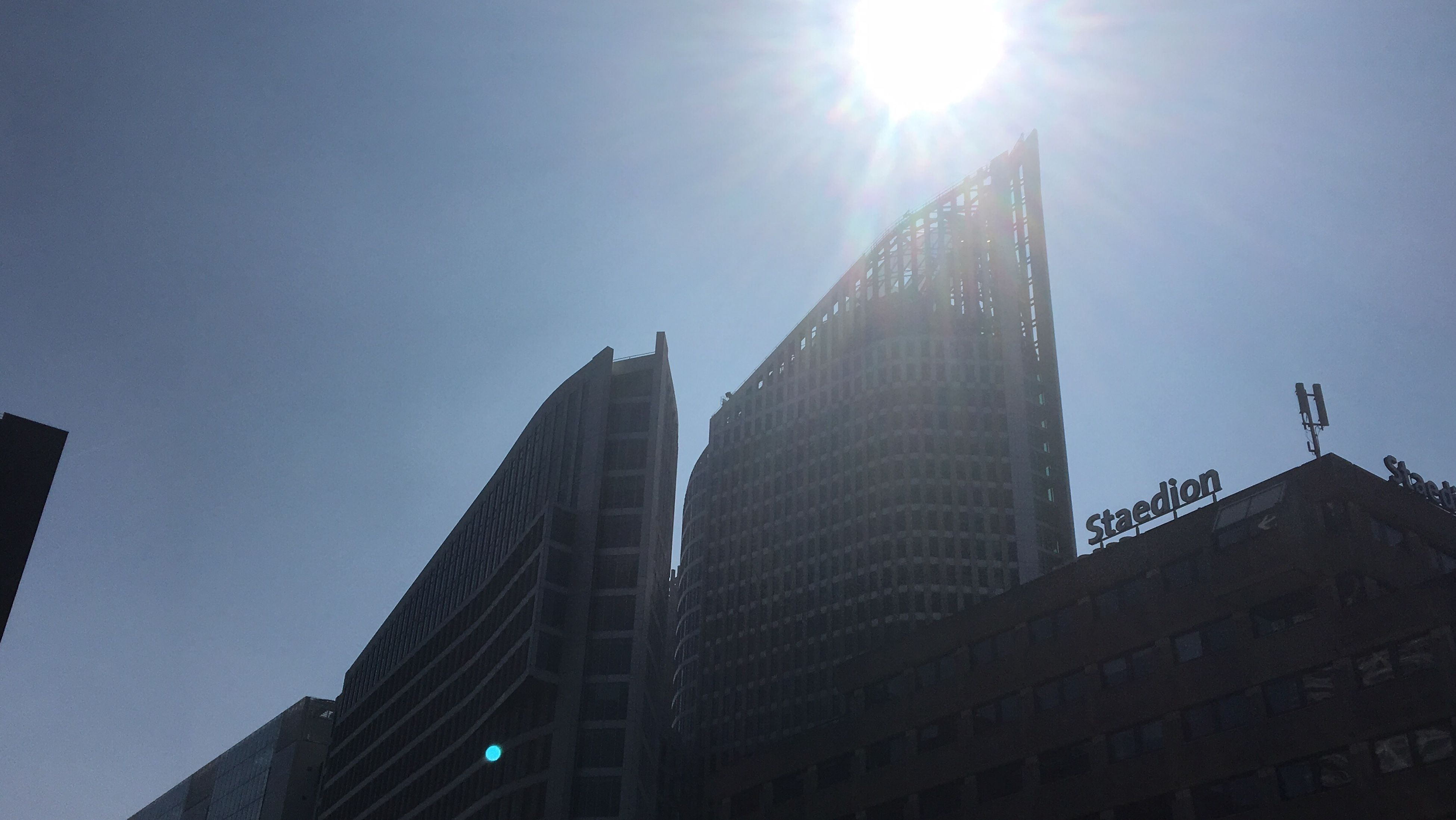 lens flare, sunlight, sunbeam, architecture, sun, skyscraper, built structure, building exterior, modern, low angle view, city, day, travel destinations, outdoors, no people, corporate business, sky