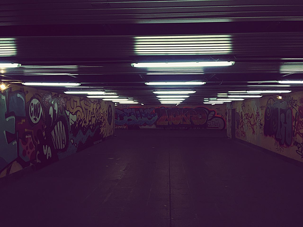 illuminated, graffiti, ceiling, lighting equipment, empty, the way forward, no people, indoors, built structure, night, architecture