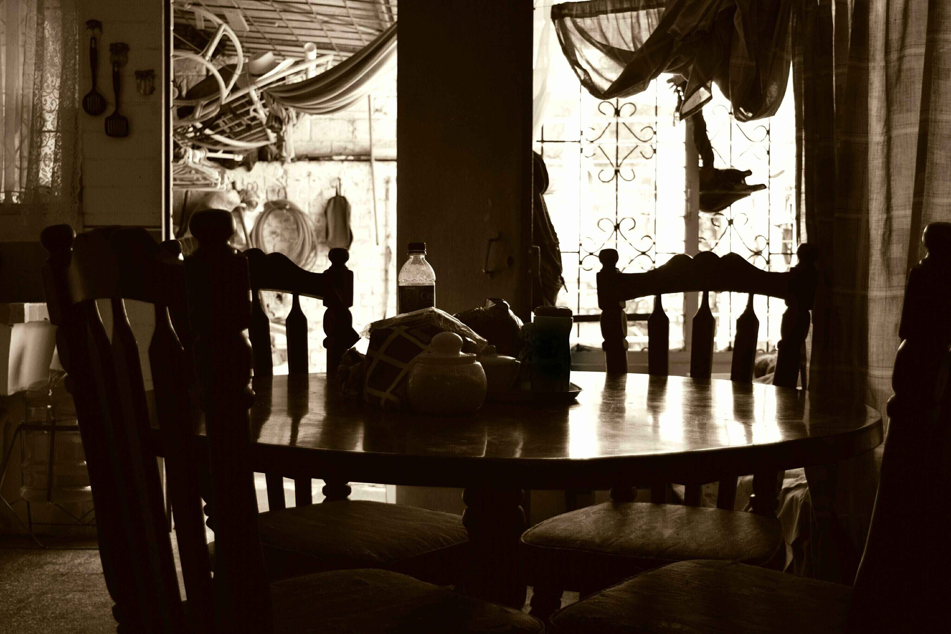 indoors, chair, table, restaurant, window, sitting, home interior, shadow, sunlight, silhouette, men, architecture, built structure, glass - material, lifestyles, absence, reflection, person, empty