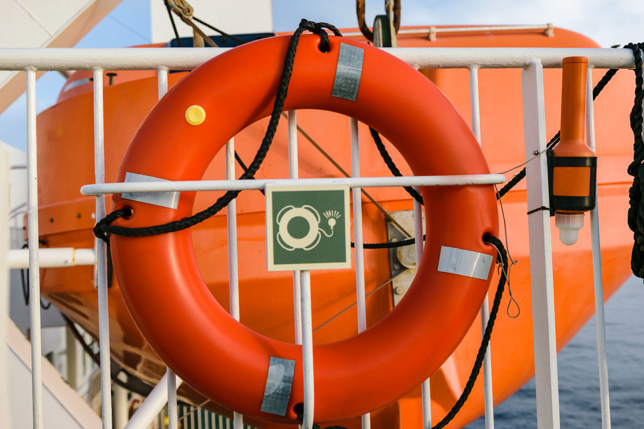 A red lifebelt on a ferry mounted on a fence in front of a lifeboat. Buoy Circle Equipment Ferry Life Belt Lifebelt Lifeboat Lifebuoy Lifeguard  Lifesaver No People Orange Color Protection Railing Rescue Residential Building Ring Rope Safety Save Sea Sos Water