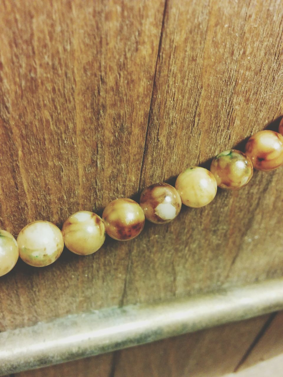 Close-Up Of Bead String On Wood