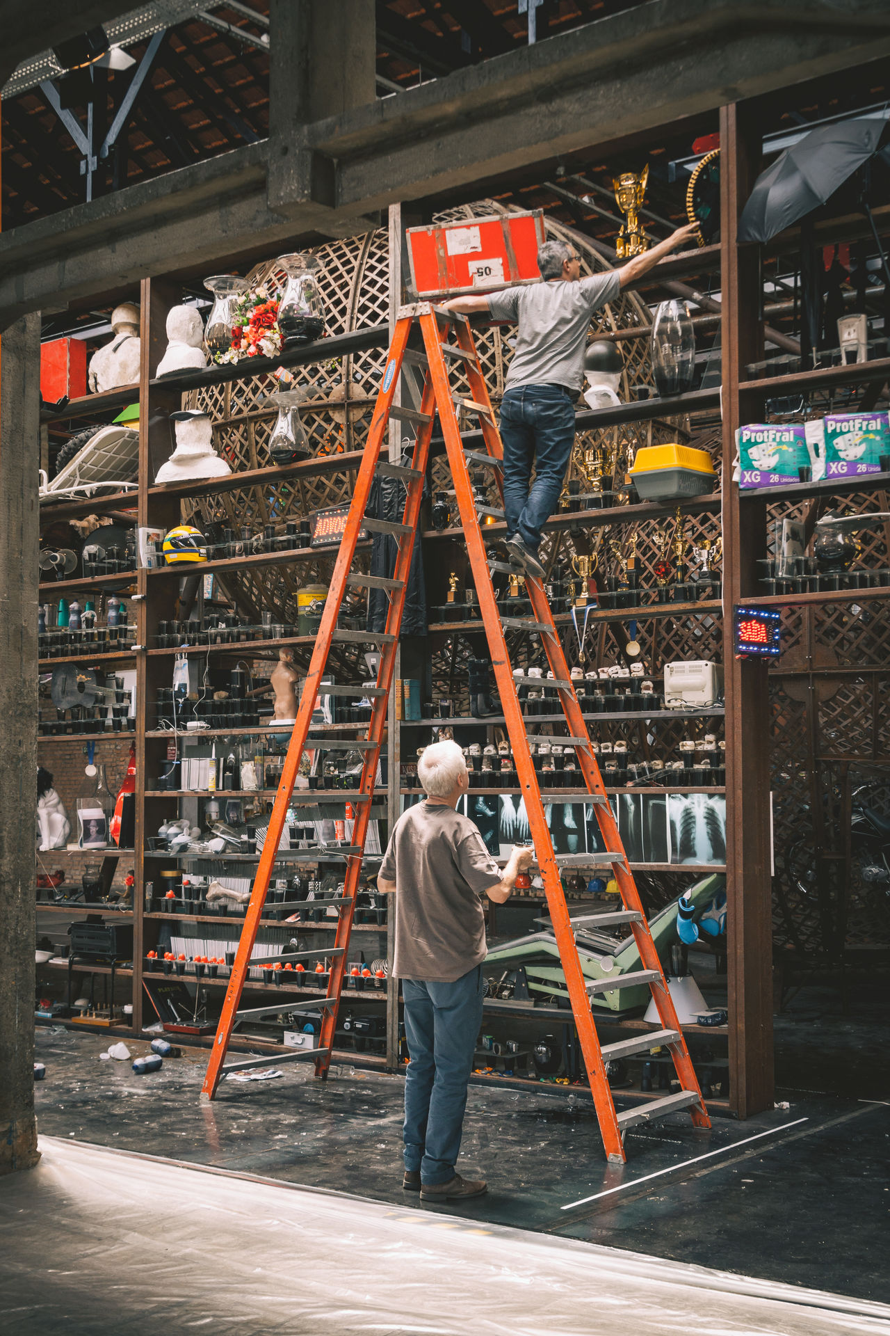 Hard to work to get everything sorted up there. Adult Adults Only Architecture Casual Clothing Day Exhibition Hardhat  Helmet Holding Indoors  Industry Ladder Mature Adult Men Occupation Occupational Safety And Health Only Men People Real People Rear View Reflective Clothing Shelf Standing The Street Photographer - 2017 EyeEm Awards Working
