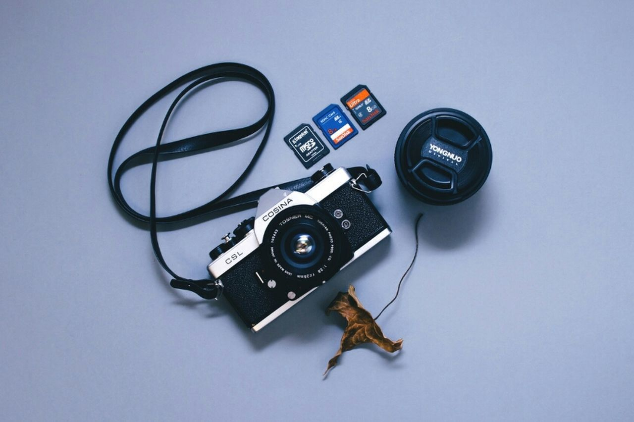 camera - photographic equipment, photography themes, still life, table, technology, high angle view, film reel, studio shot, no people, film industry, old-fashioned, directly above, indoors, white background, retro styled, digital single-lens reflex camera, camera, movie camera, photographing, close-up, slr camera, television camera, day