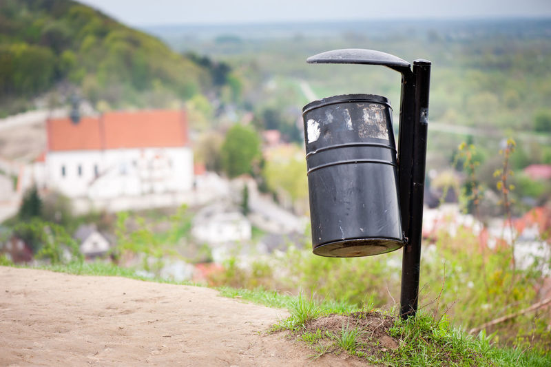 Single black metal empty rubbish bin on the hill and blurred dale view in Kazimierz Dolny, Poland, lubelskie. Object stick in tourist place destination with view at all town valley landscape, horizontal orientation, nobody. Basket Discard Garbage Garbage Bin Garbage Can Hill KAZIMIERZ DOLNY Kazimierzdolny Landscape Litter Nature No People Outdoors Poland Rubbish Bin Town Vale Valley Village