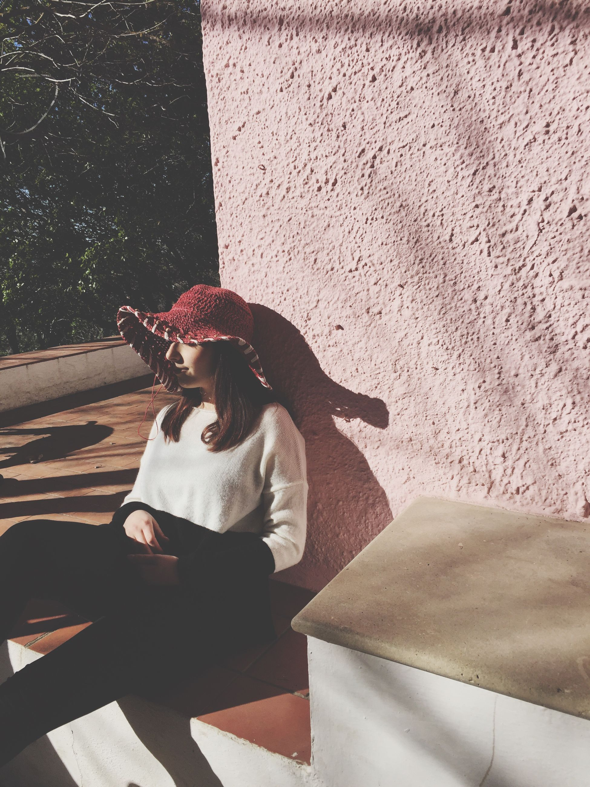 lifestyles, full length, casual clothing, leisure activity, standing, shadow, young adult, wall - building feature, young women, high angle view, built structure, person, architecture, sunlight, sitting, day, walking, three quarter length