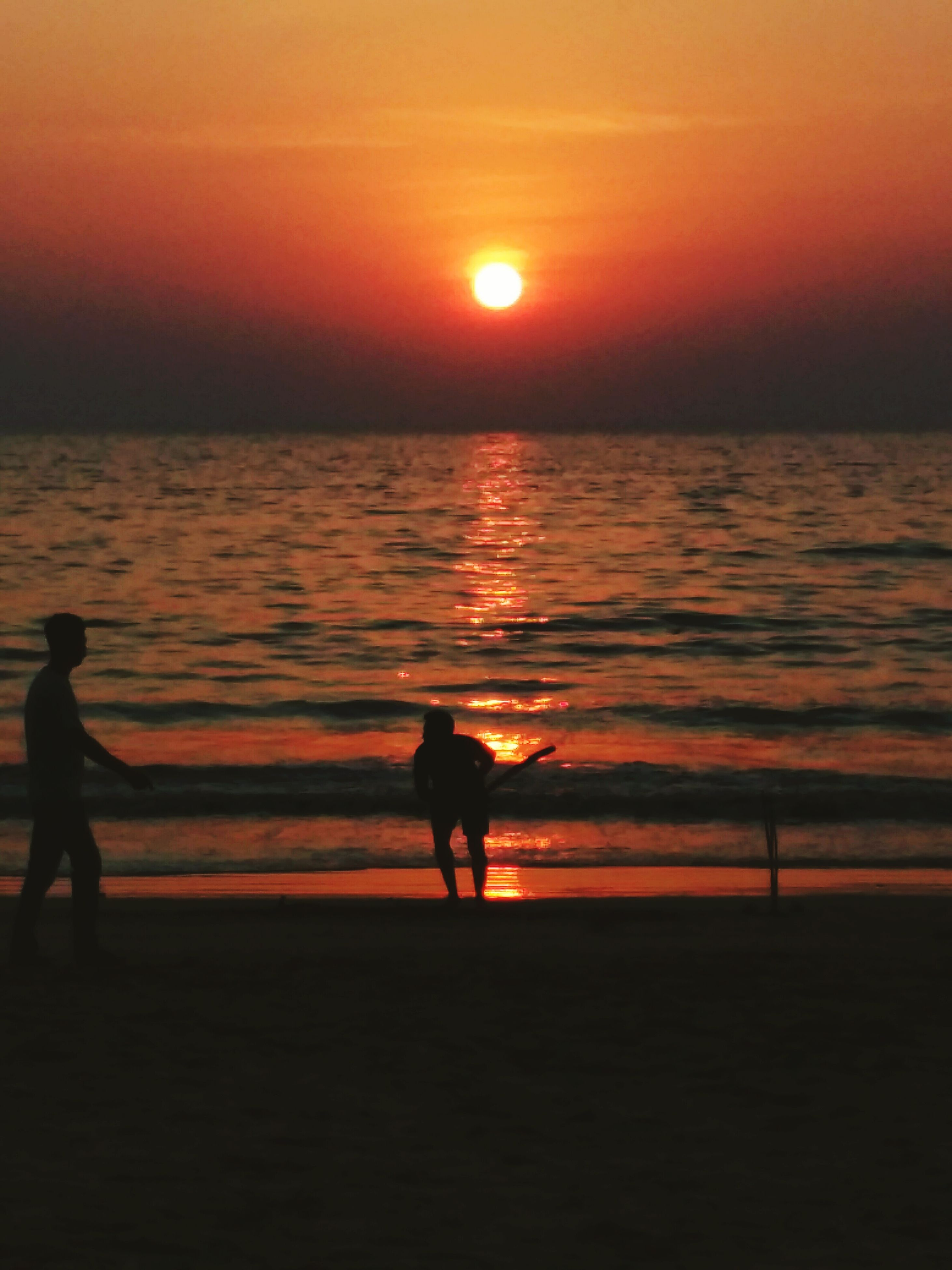 sunset, water, silhouette, sea, orange color, sun, horizon over water, scenics, beach, beauty in nature, tranquil scene, reflection, men, tranquility, leisure activity, lifestyles, sky, shore, idyllic